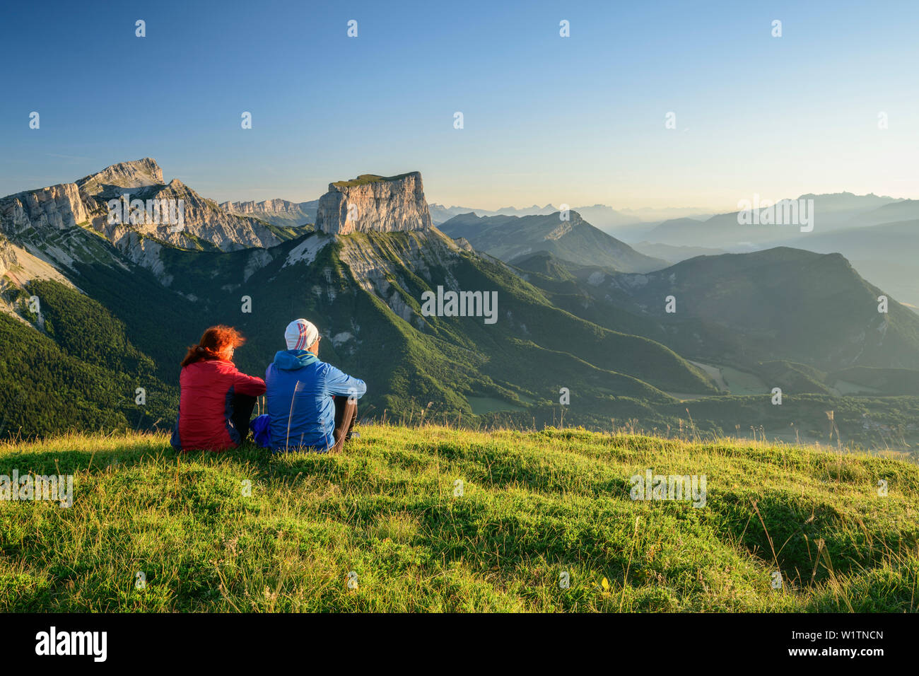 A man and a woman sitting on meadow and views of Grand Veymont and Mont Aiguille in the morning light, from the Tête Chevalier, Vercors, Dauphine, Dau - Stock Image