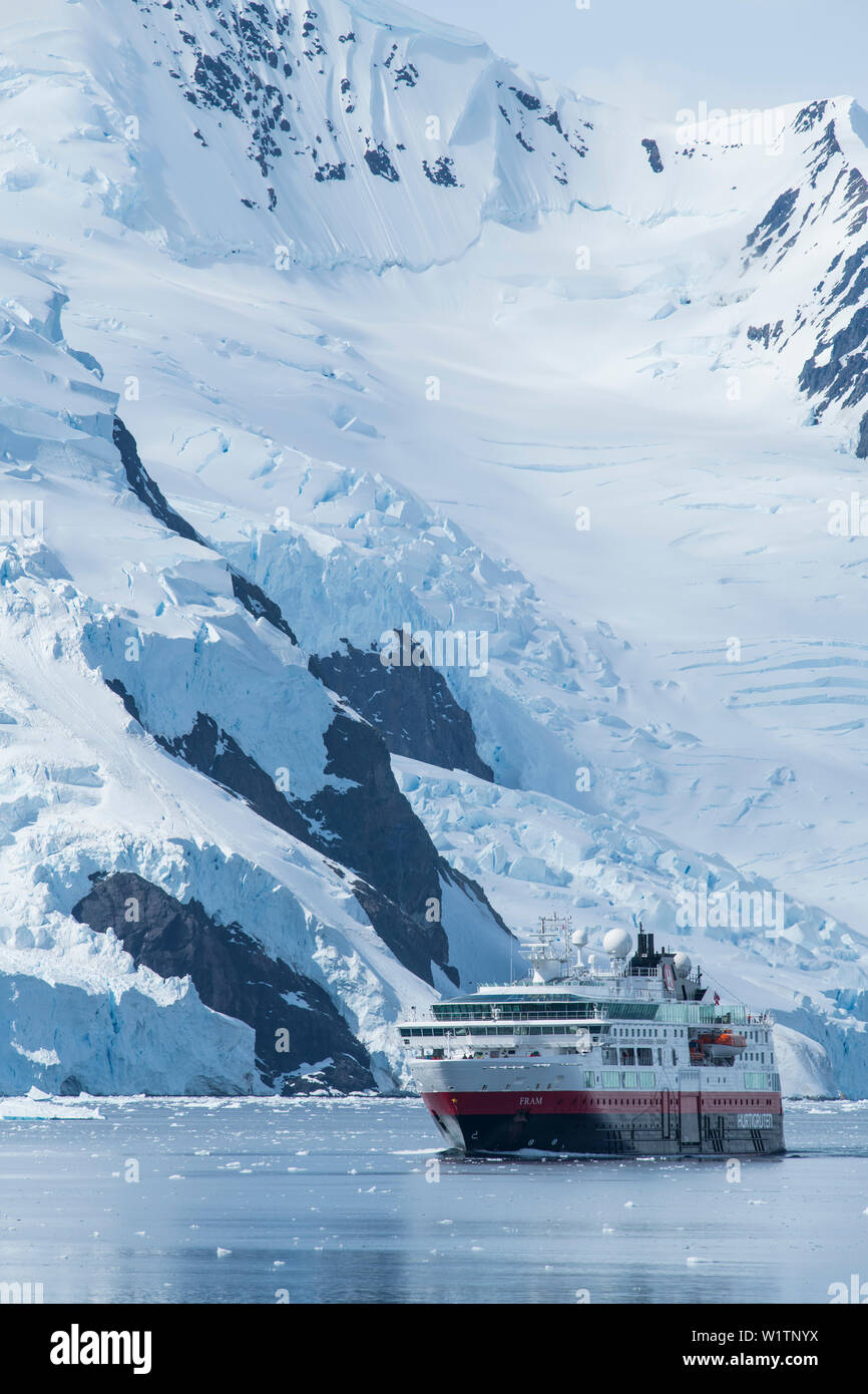 The Fram (Hurtigruten Group) makes way with a backdrop of steep snow and glacier covered mountains, Neko Harbour, Graham Land, Antarctica Stock Photo