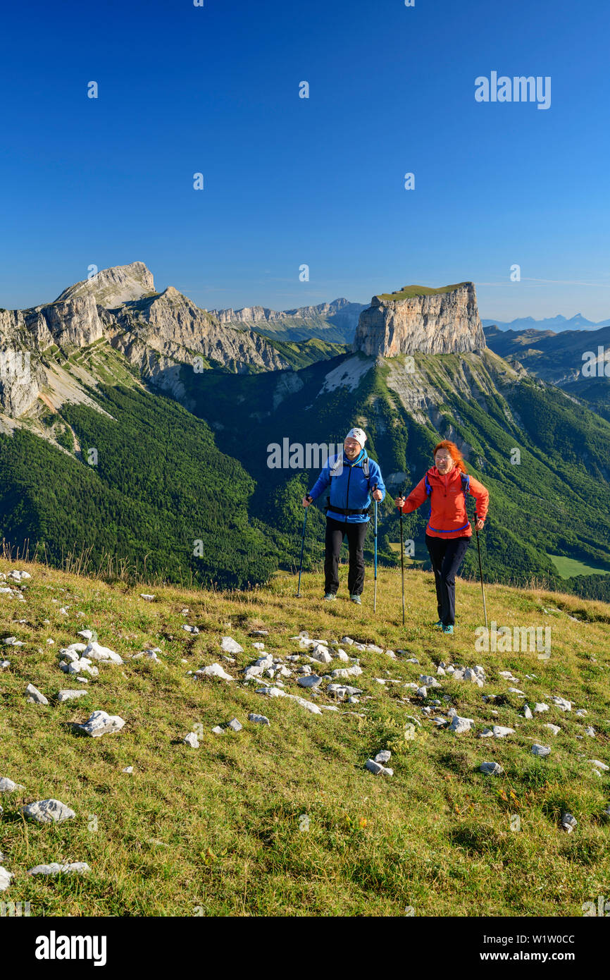 A man and a woman to climb up to the Tête Chevalier, Grand Veymont and Mont Aiguille in the background, Tête Chevalier, Vercors, Dauphine, Dauphine, I - Stock Image