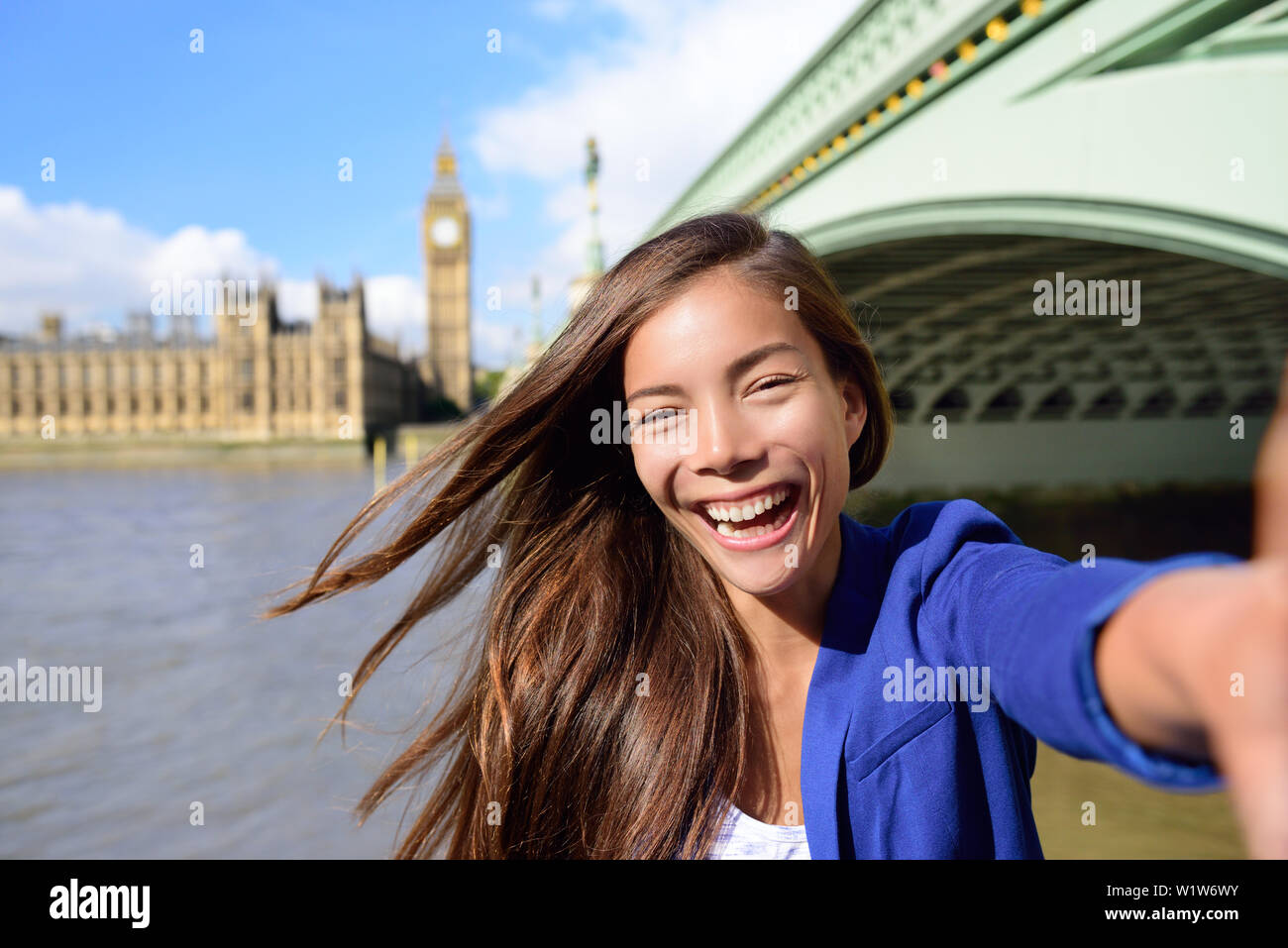 London travel selfie businesswoman. Joyful young casual business woman smiling at camera with Thames river, Big Ben and Westminster bridge background. Asian tourist using smartphone for picture. - Stock Image