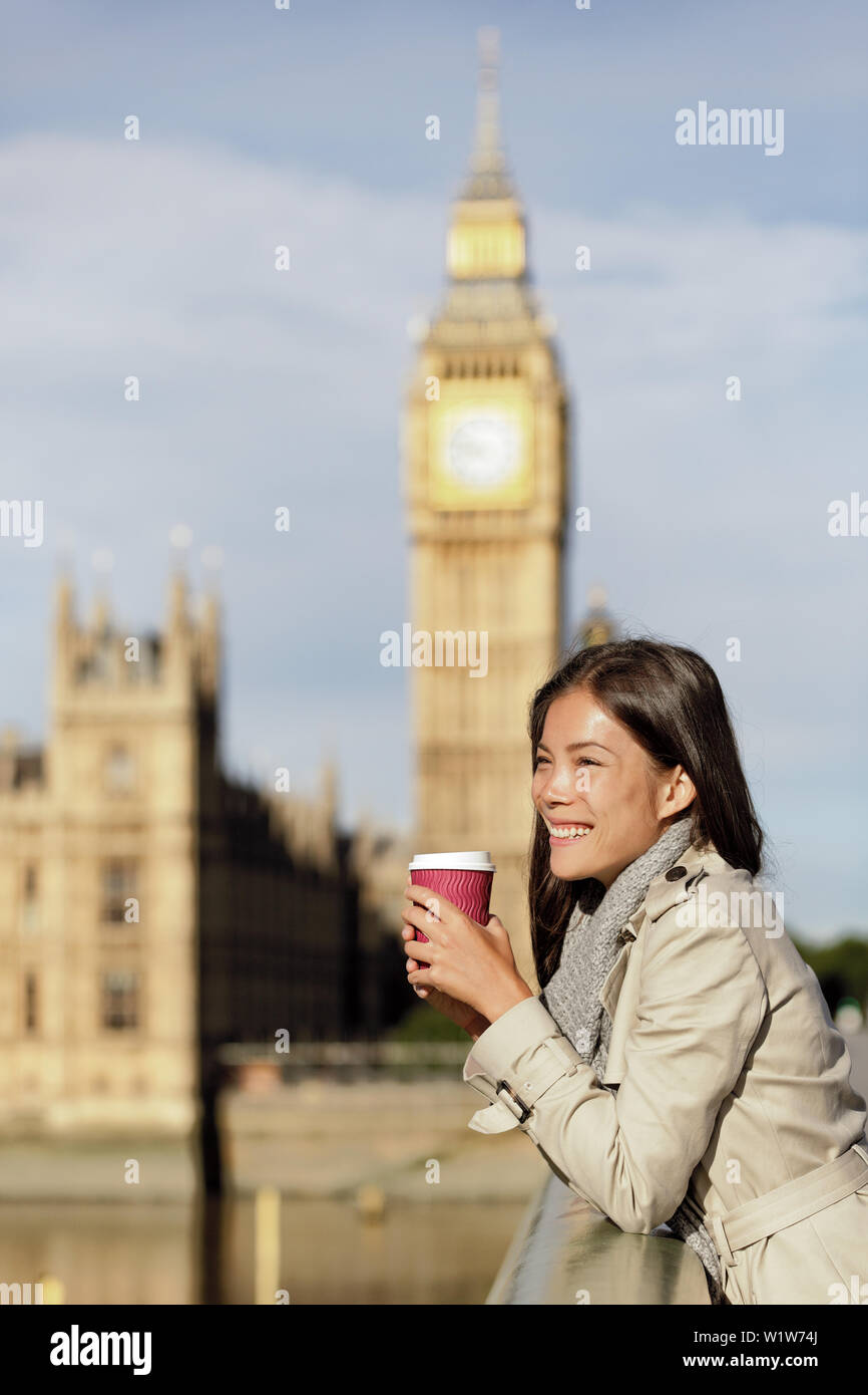 London city business woman drinking morning coffee looking over Westminster bridge near Big Ben, UK. Urban Asian businesswoman or female tourist happy in fall/spring, filtered image with golden sun. - Stock Image
