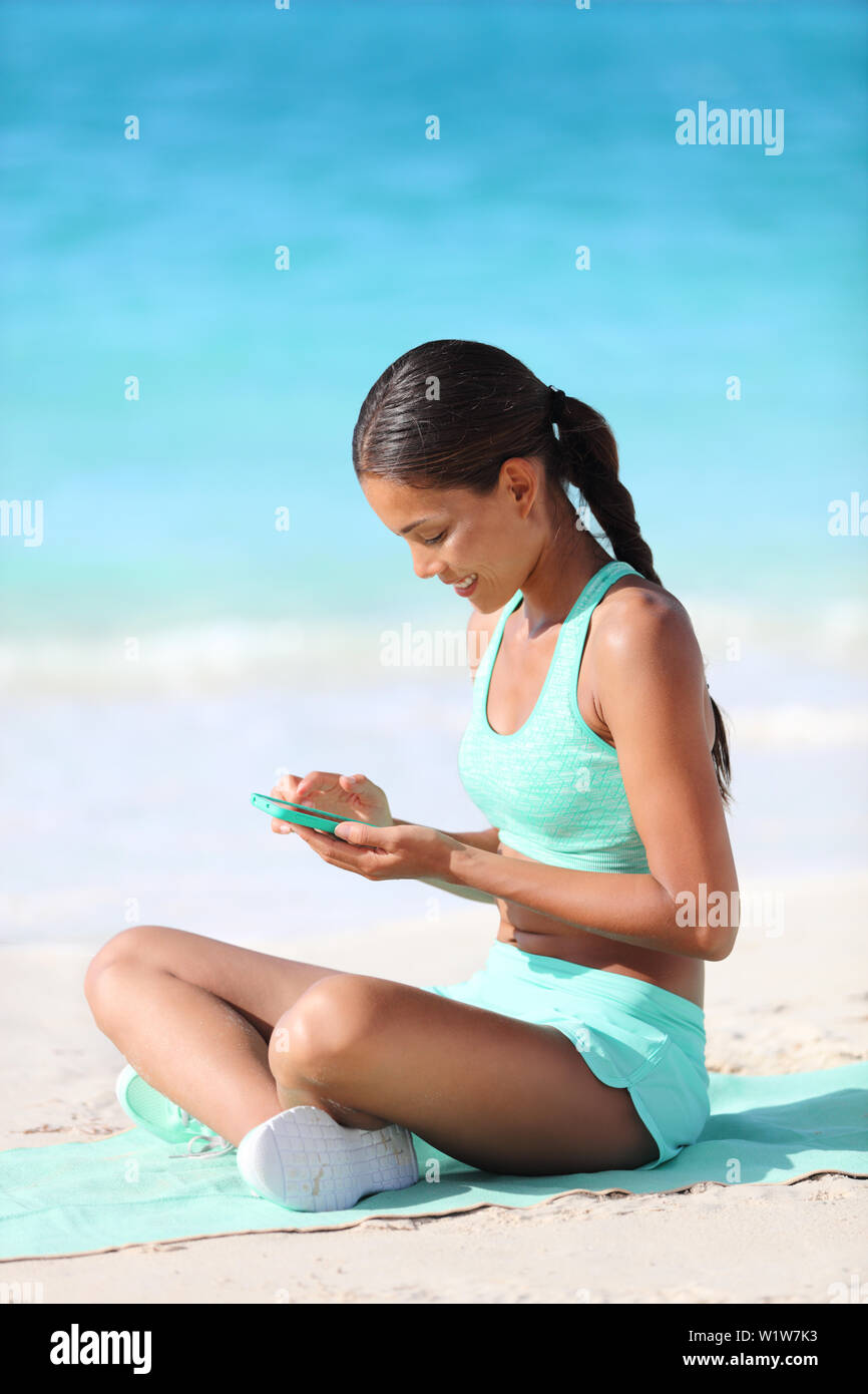 Fit girl using fitness app on phone during travel holidays on beach texting or posting on social media online. Healthy sporty Asian woman living a happy active life exercising on towel. - Stock Image