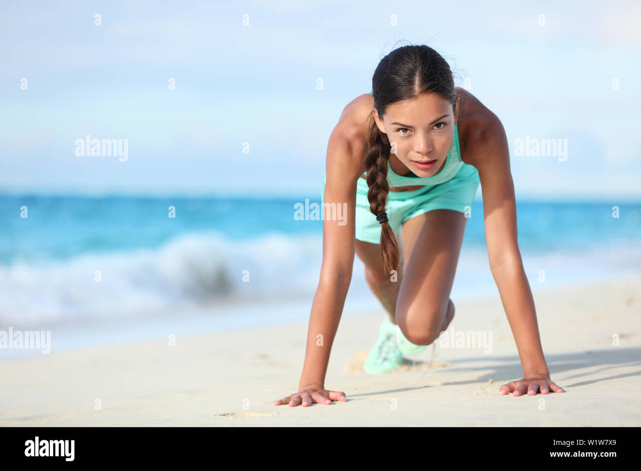 Fitness athlete working out body core with bodyweight exercises. Strong fit woman training cardio and exercising abdominal muscles with mountain climber workout exercise on beach. - Stock Image