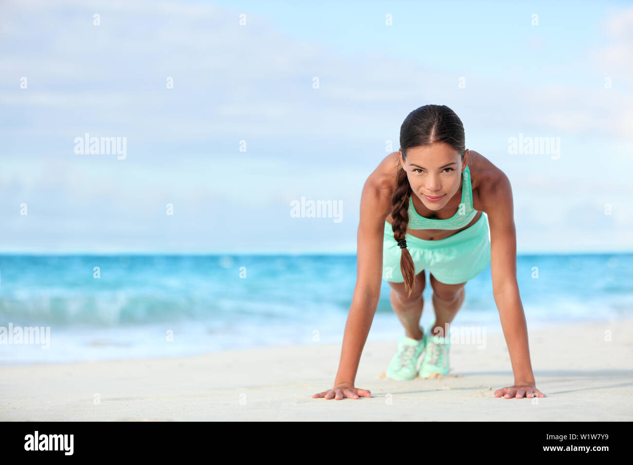 Fitness beach woman smiling planking doing yoga exercises. Happy Asian girl training her abs exercising her core muscles with the plank pose. - Stock Image