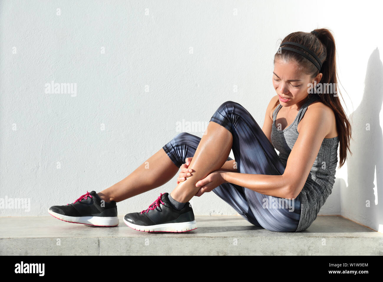Running injury leg accident- sport woman runner hurting holding painful sprained ankle in pain. Female athlete with joint or muscle soreness and problem feeling ache in her lower body. - Stock Image