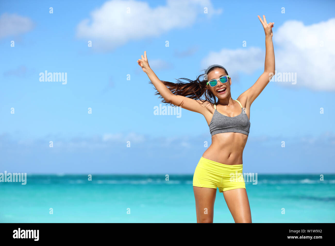 Happy cheerful fitness woman in sunglasses winning arms up doing v hand signs. Fit girl with slim body on sunny beach with raised arm showing peace sign in happiness of weight loss after workout. Stock Photo