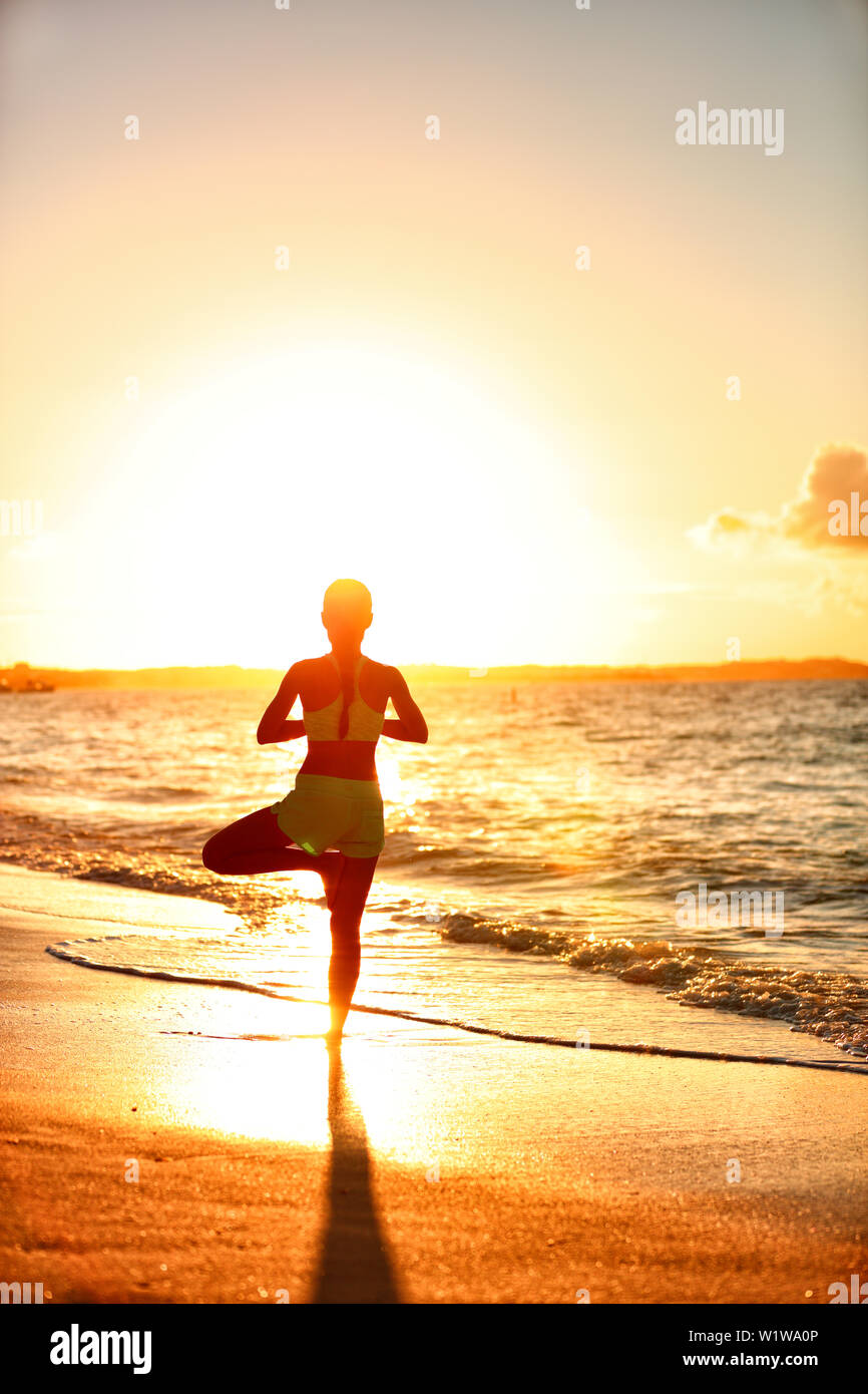 Meditation woman practicing Vriksasana tree yoga pose on beach at sunset. Serene young adult silhouette in morning sun flare balancing meditating doing a body workout. Wellness concept. Stock Photo