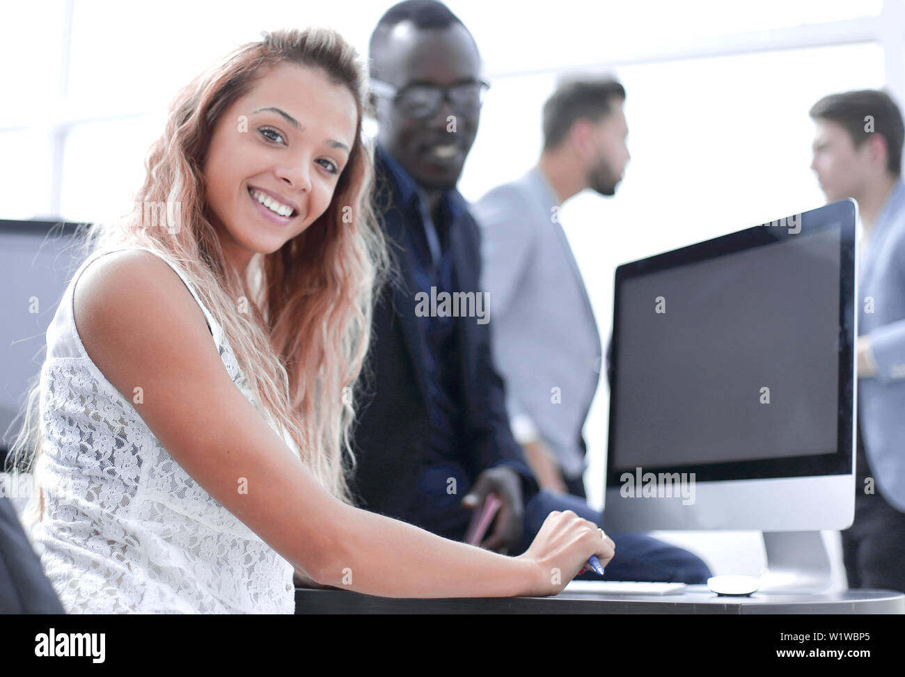 young business woman sitting at office Desk - Stock Image