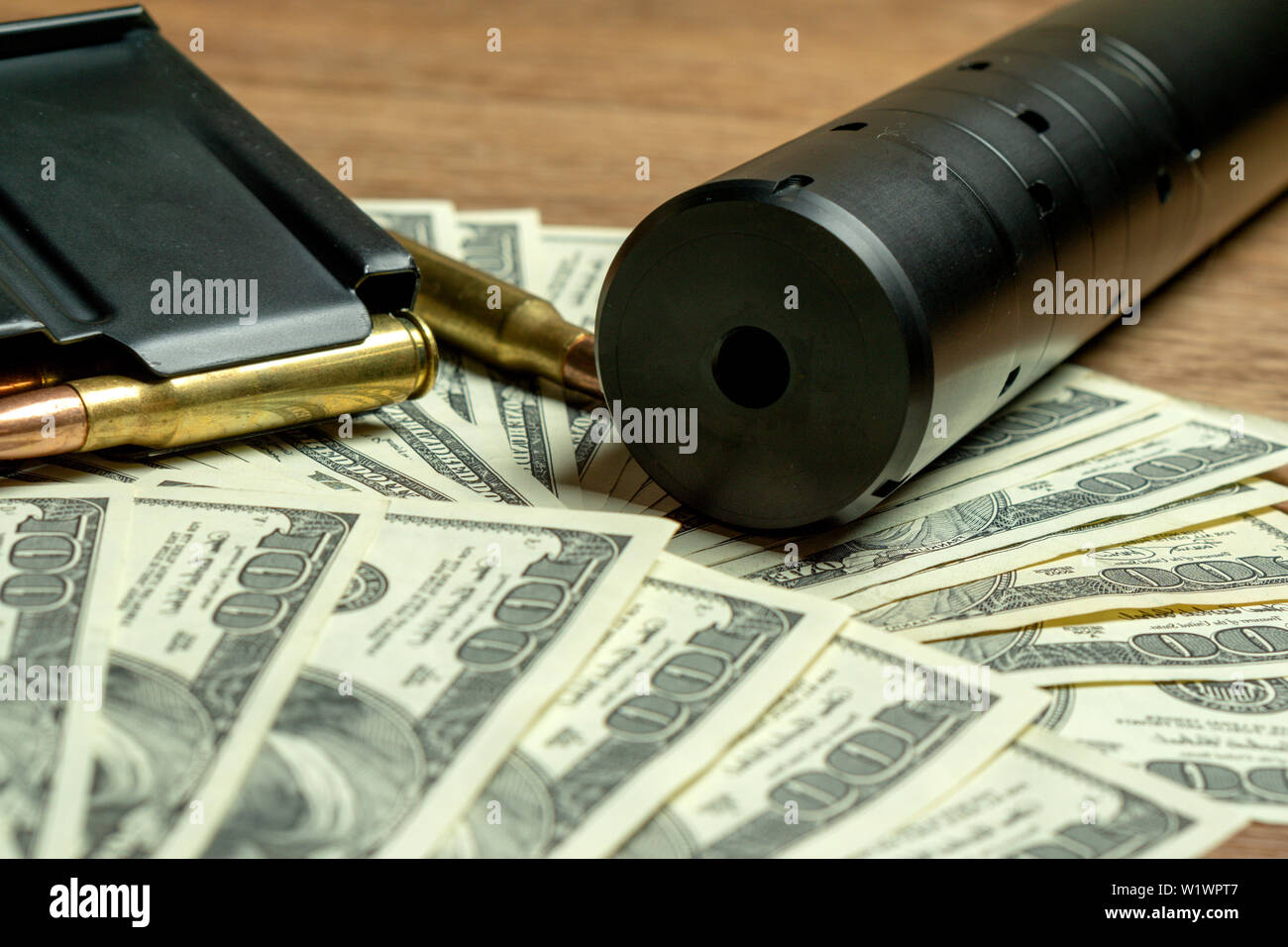 Rifle barrel, suppressor and cartridges on money. Concept for crime, contract killing, paid assassin, terrorism, war, global arms trade, weapons sale - Stock Image