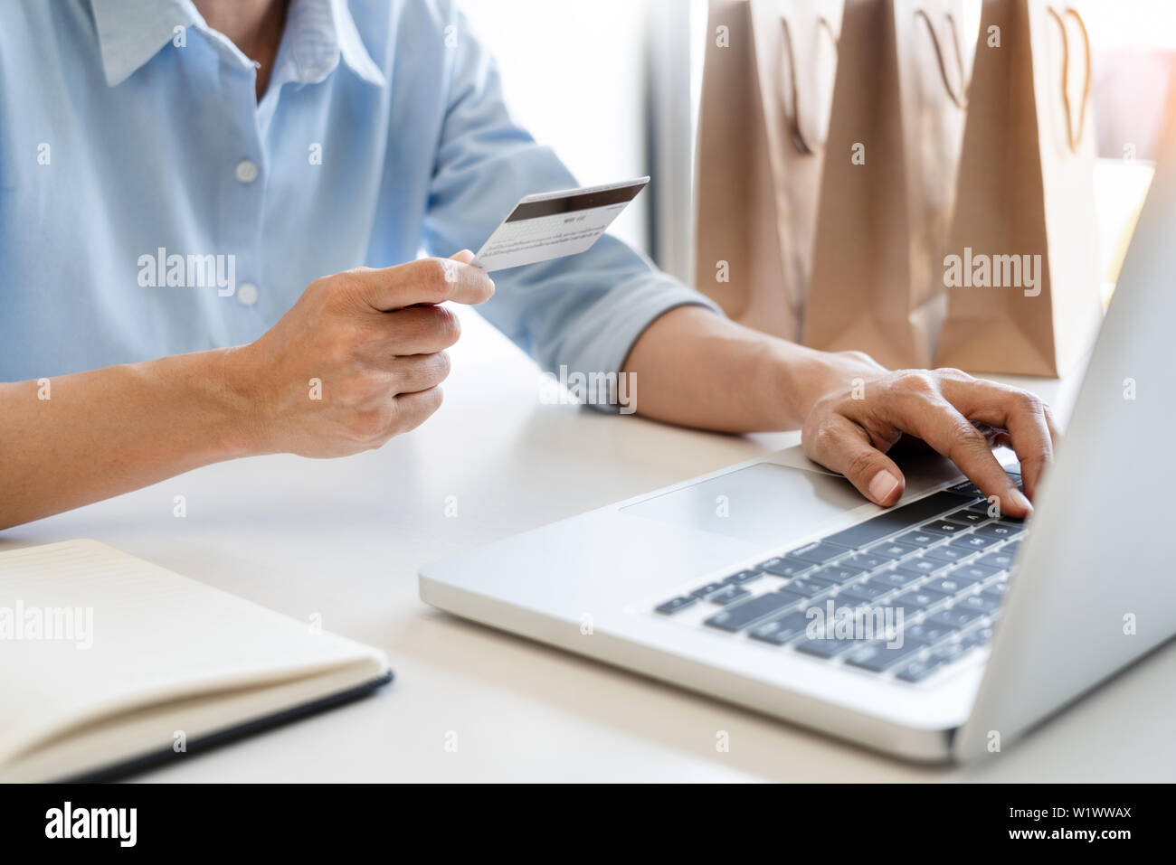 Man holding credit card in hand and entering security code