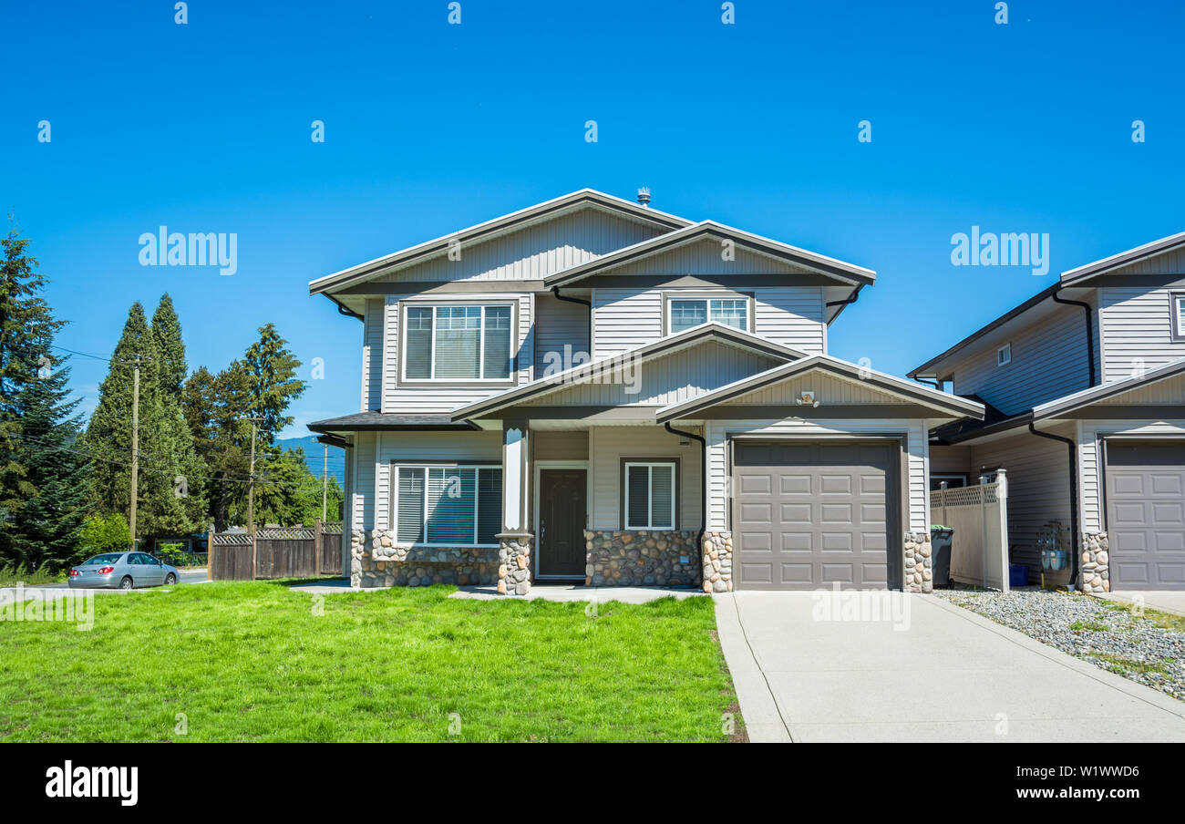 Half duplex residential building with concrete drive way and green lawn in front Stock Photo