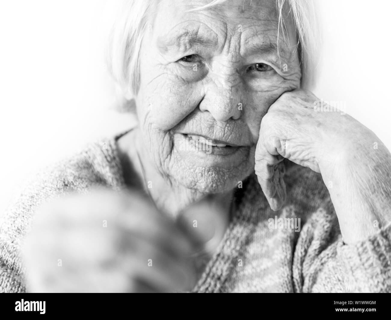 Cheerful elderly 96 years old woman sitting at table at home happy with a coin in her hand. Saving for retirement and financial planing concept in - Stock Image