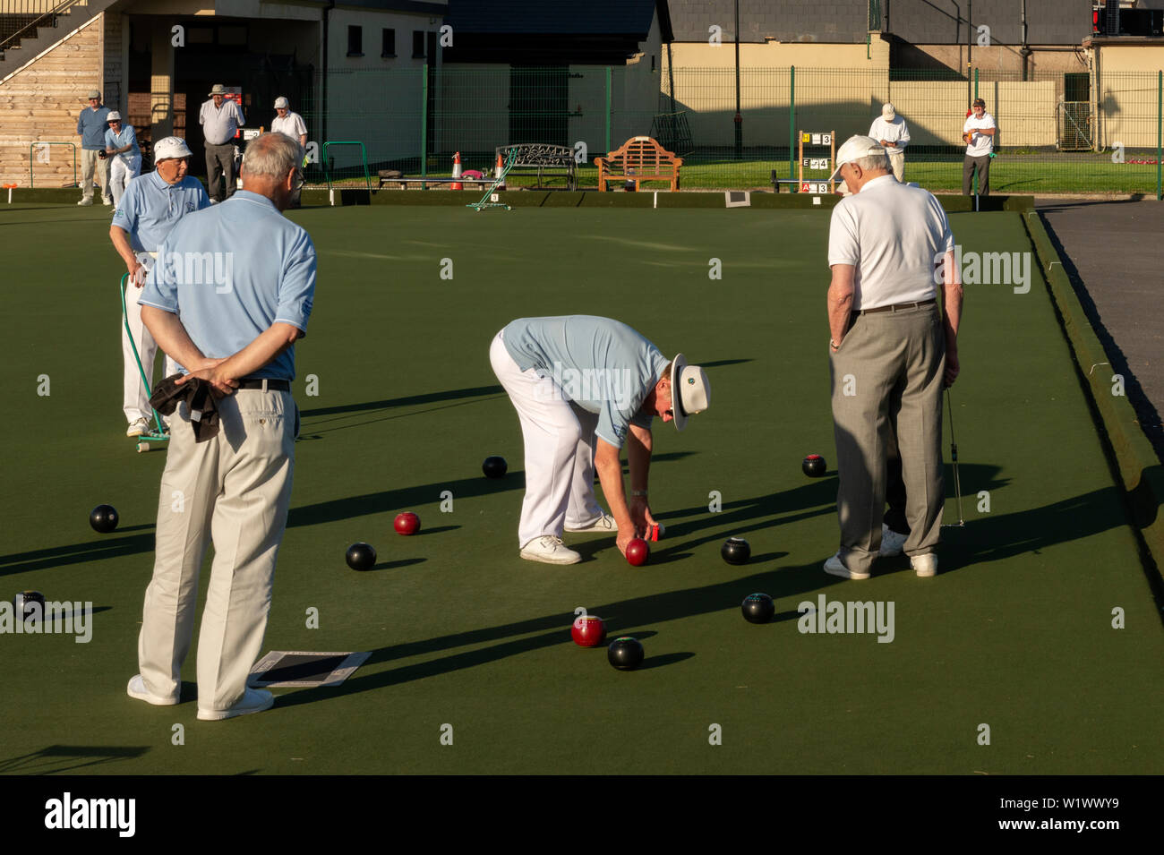 Several senior men playing lawn bowls at The Causeway Tennis and Bowls Club in late afternoon with low sunset light Dungarvan Ireland - Stock Image