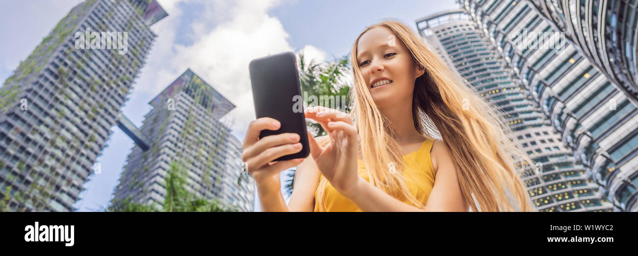 Woman Tourist using navigation app on the mobile phone. Navigation map on a smartphone in a big city BANNER, LONG FORMAT Stock Photo