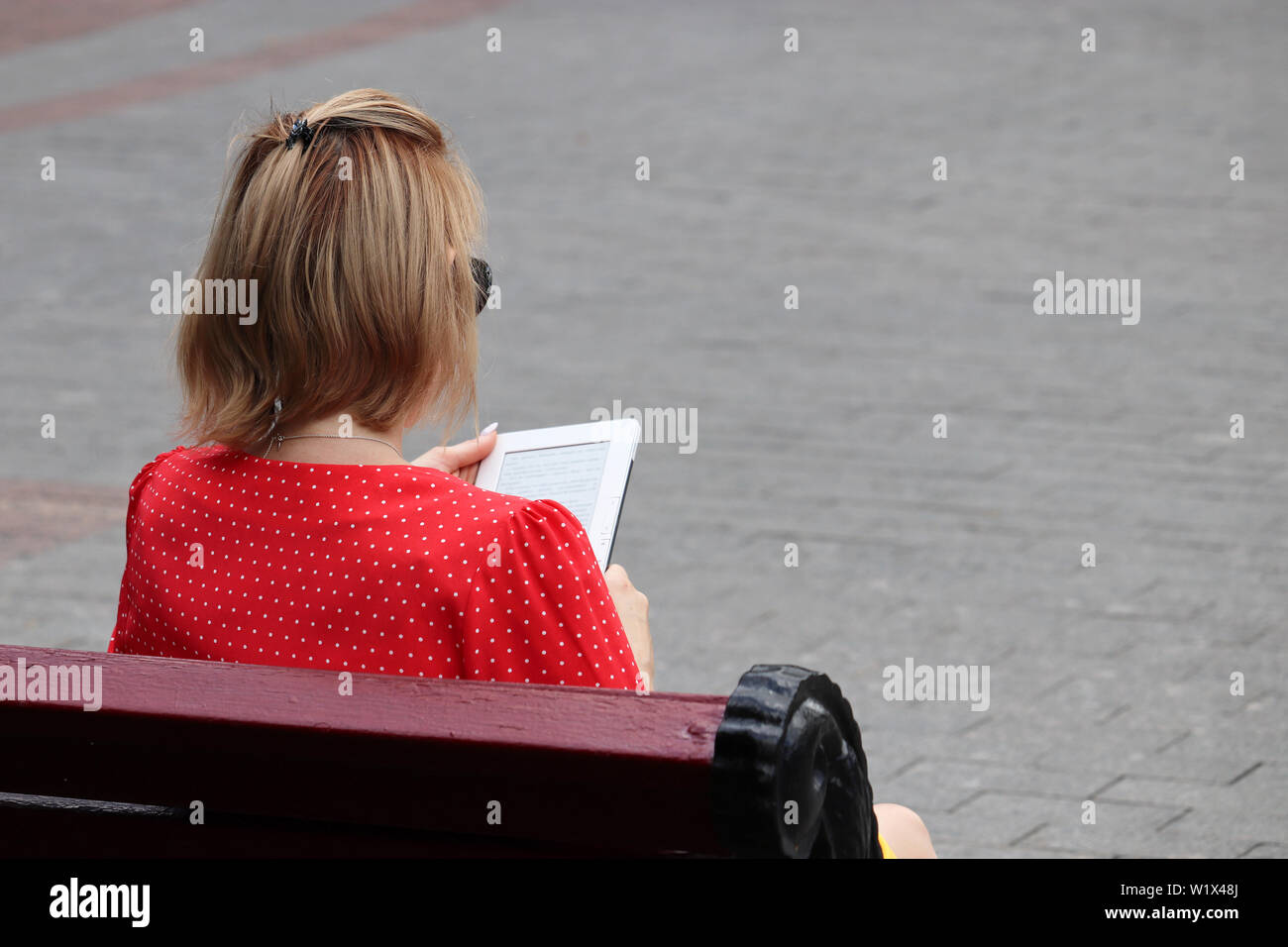 Young woman reads ebook on sitting on a bench on a city street. Concept of student, education, summer leisure - Stock Image