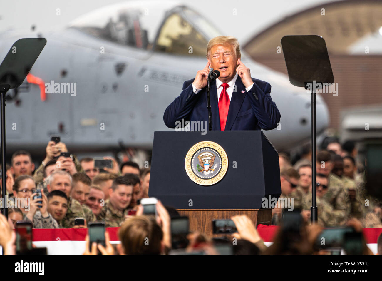 Prsident Donald J. Trump shields his ears from the noise of the crowd during an event at Osan Air Base, Republic of Korea, June 30, 2019.  Every service branch serving under U.S. Forces Korea was represented in the crowd during the presidential visit to the peninsula.  (U.S. Air Force photo by 1st Lt. Daniel de La Fé) Stock Photo