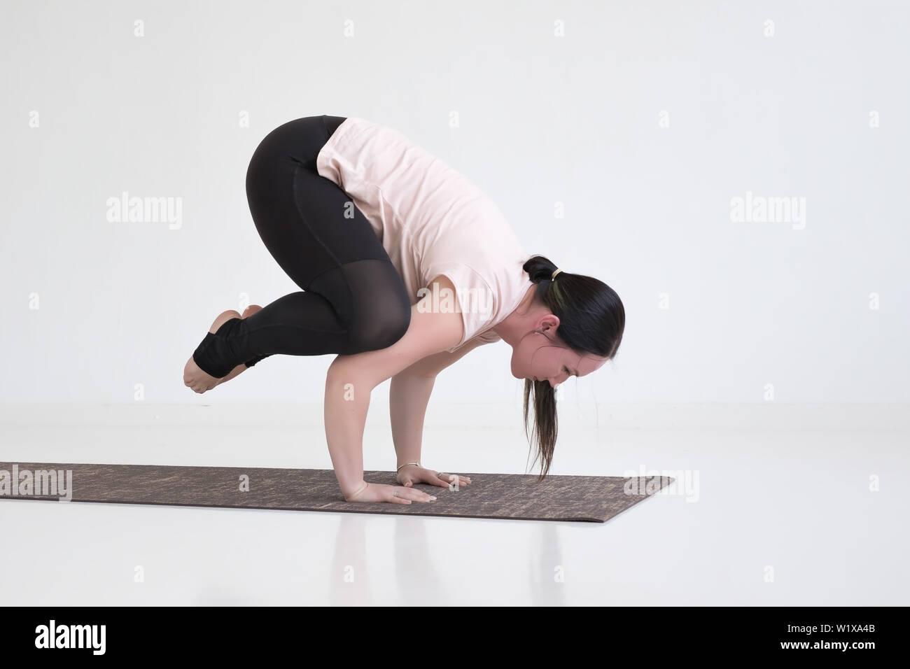 Young woman practicing yoga, doing Crane exercise, Bakasana pose - Stock Image