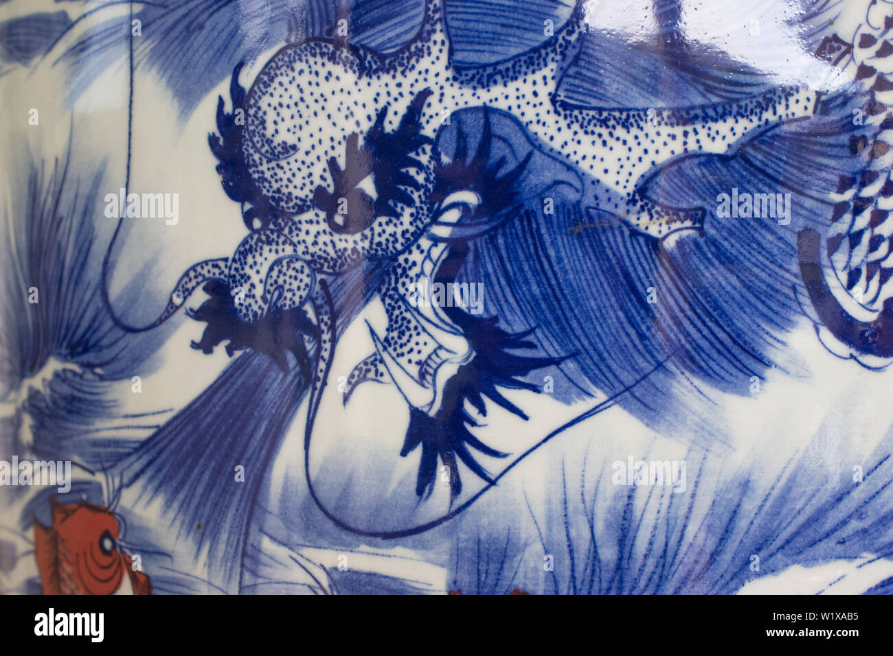 Chinese or Asian artistic  blue and white depiction of a dragon and Koi fish on a glossy or shiny ceramic surface of an urn or vase close up - Stock Image