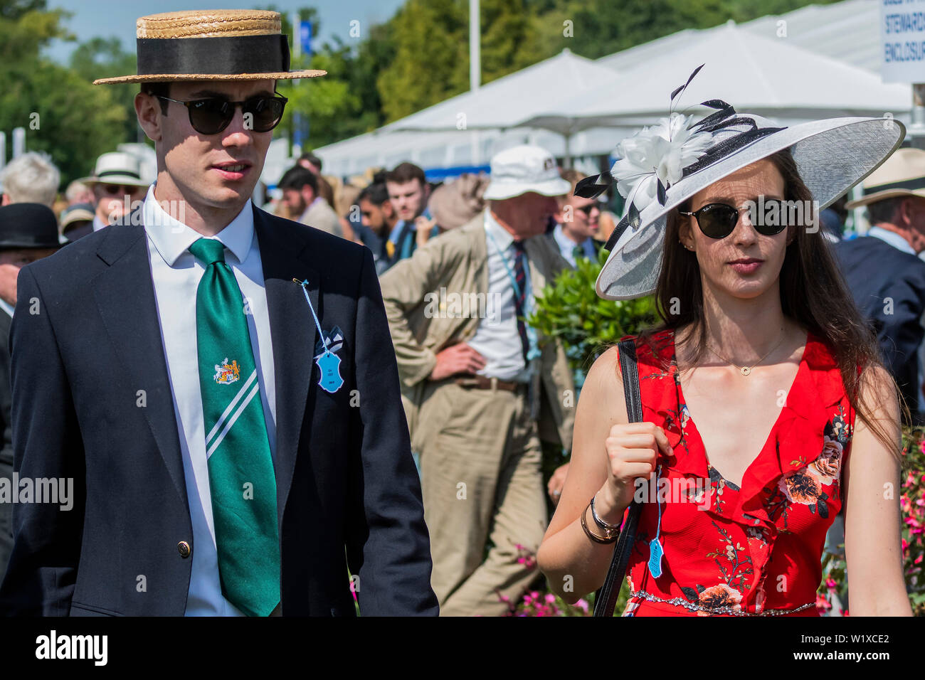 Henley-on-Thames, UK. 3rd July 2019. Big hats and rowing blazers are the order of the day as spectators relax in in the Stewards Enclosure along the river bank - Rowing at the 2019 Henley Royal Regatta, Henley-on-Thames. Credit: Guy Bell/Alamy Live News - Stock Image