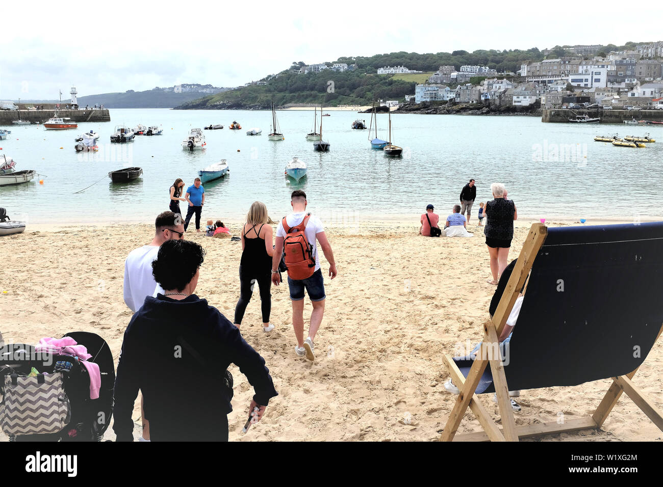 St. Ives, Cornwall, UK. June 24, 2019. Holidaymakers enjoying the sands overlooking the Harbor with high tide at St. Ives in Cornwall, UK. Stock Photo