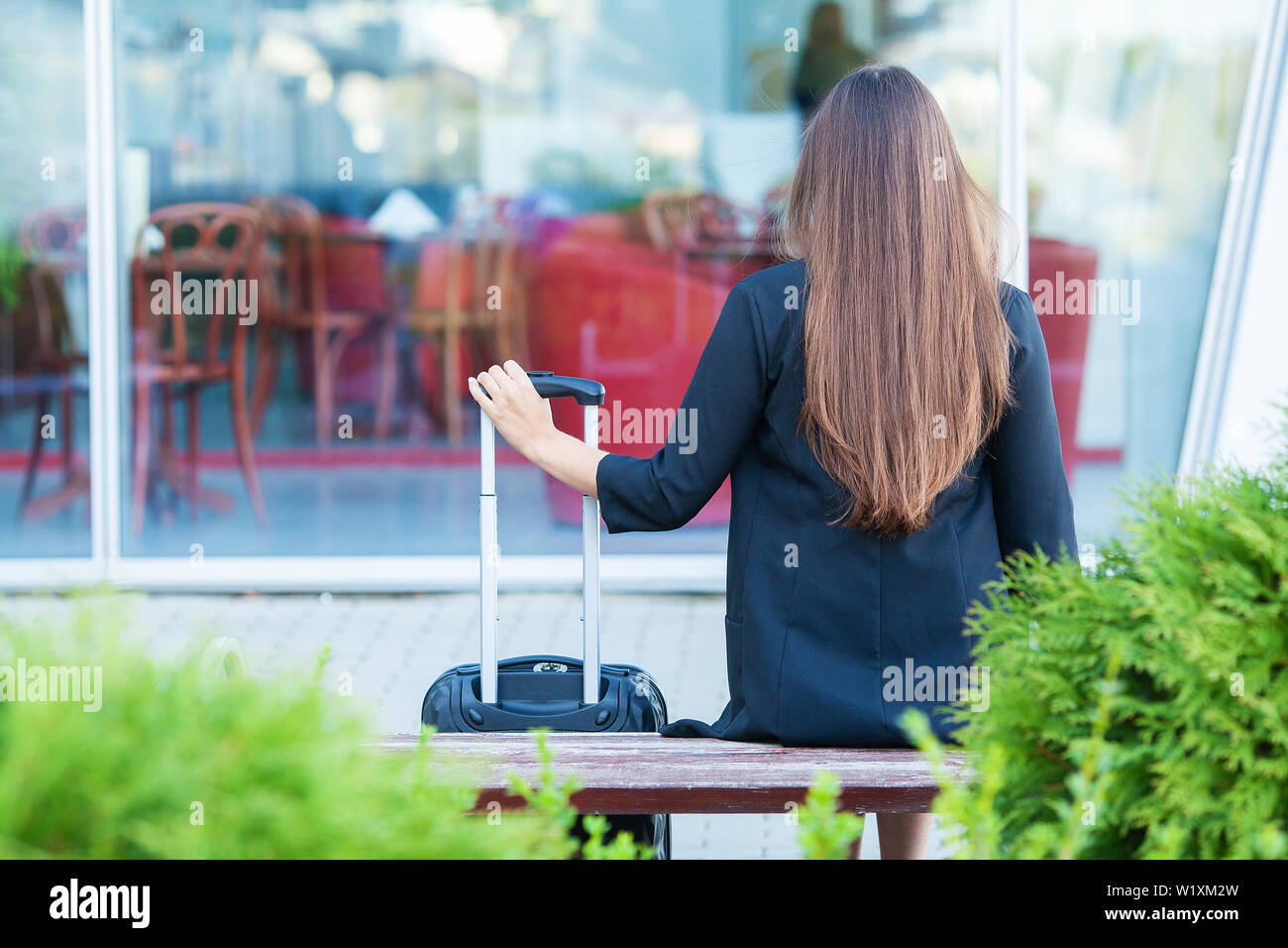 Cropped image traveler tourist woman crossed in summer casual clothes with suitcase on road in city outdoor. Girl traveling abroad to travel on - Stock Image