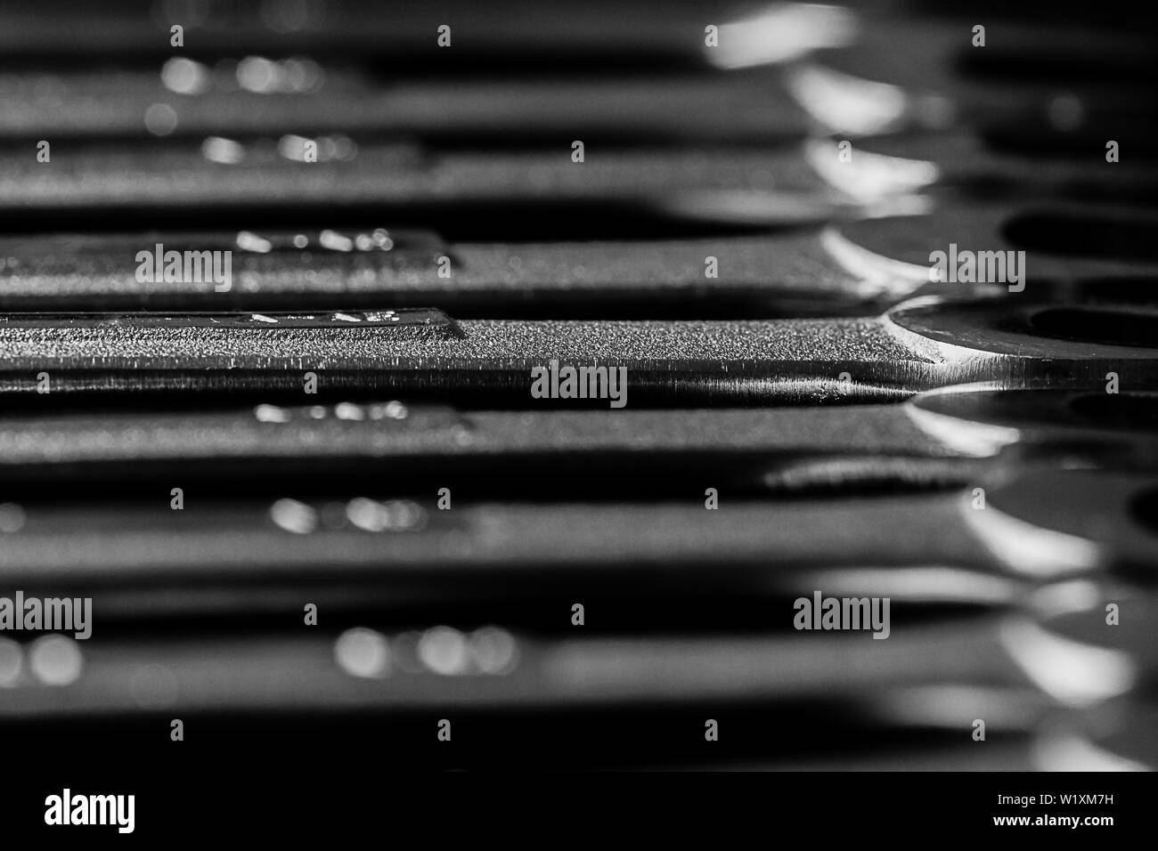 chrome wrenches laying on a table lined up with a very shallow DOF.  The wrench in the center of the image is the primary focus. Stock Photo