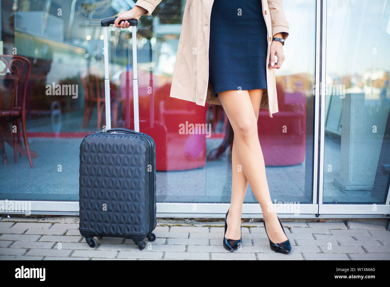 Cropped image traveler tourist woman crossed legs in summer casual clothes with suitcase on road in city outdoor. Girl traveling abroad to travel on - Stock Image