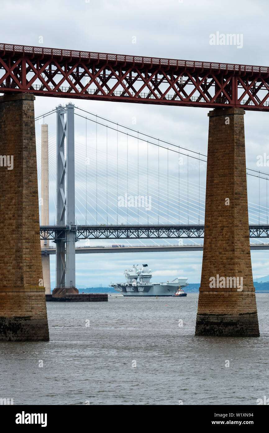 Aircraft carrier HMS Queen Elizabeth manoeuvres into position before sailing under Forth Road and Rail Bridges - from South Queensferry, Scotland, UK Stock Photo