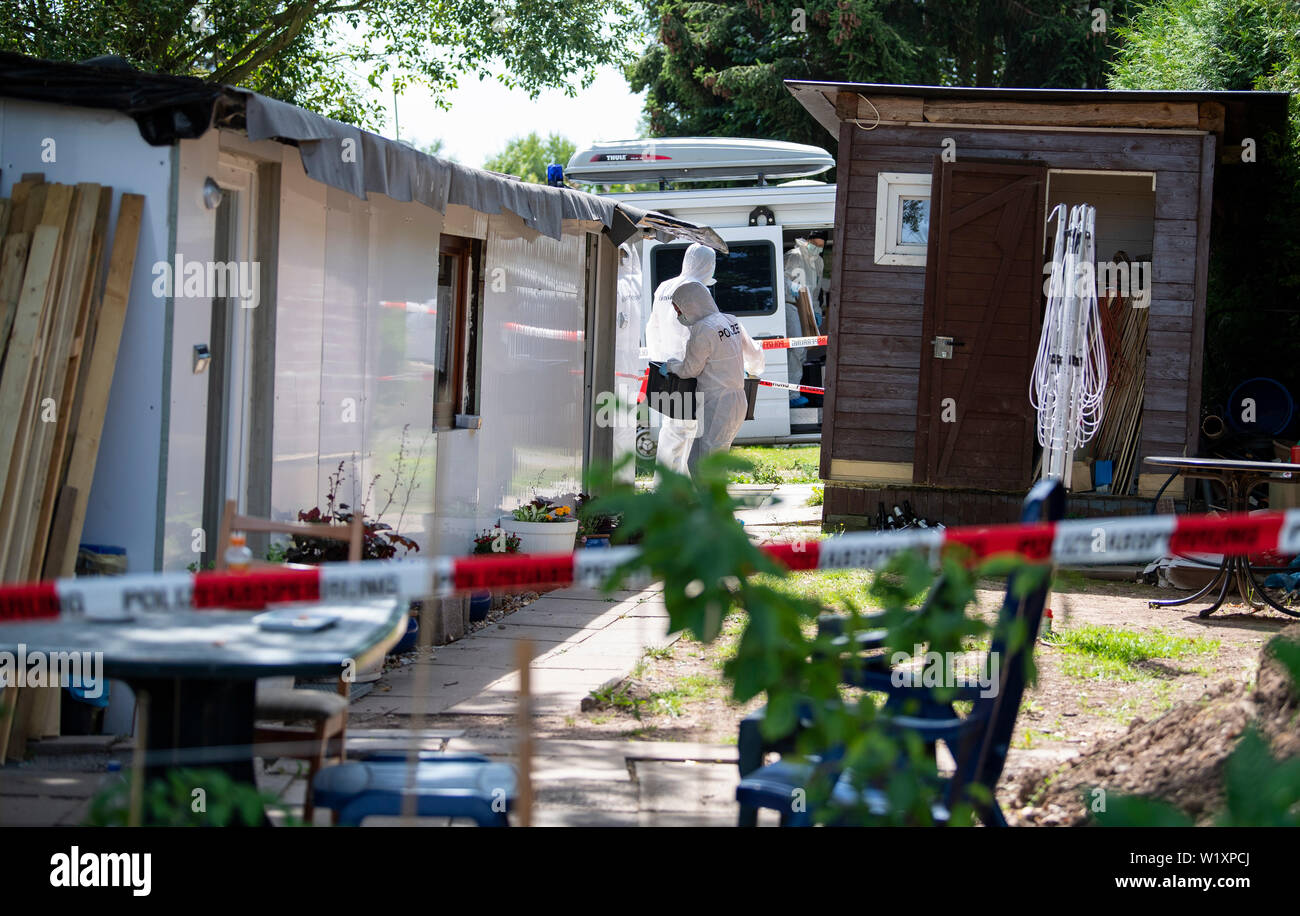 04 July 2019, North Rhine-Westphalia, Lügde: During the searches on a plot on the campsite in Lügde, forensic officers carry a box into the camping hut of a new suspect. The police search the campsite in Lügde again in connection with the hundredfold abuse. In Detmold, the process continues in parallel. Photo: Guido Kirchner/dpa - Stock Image