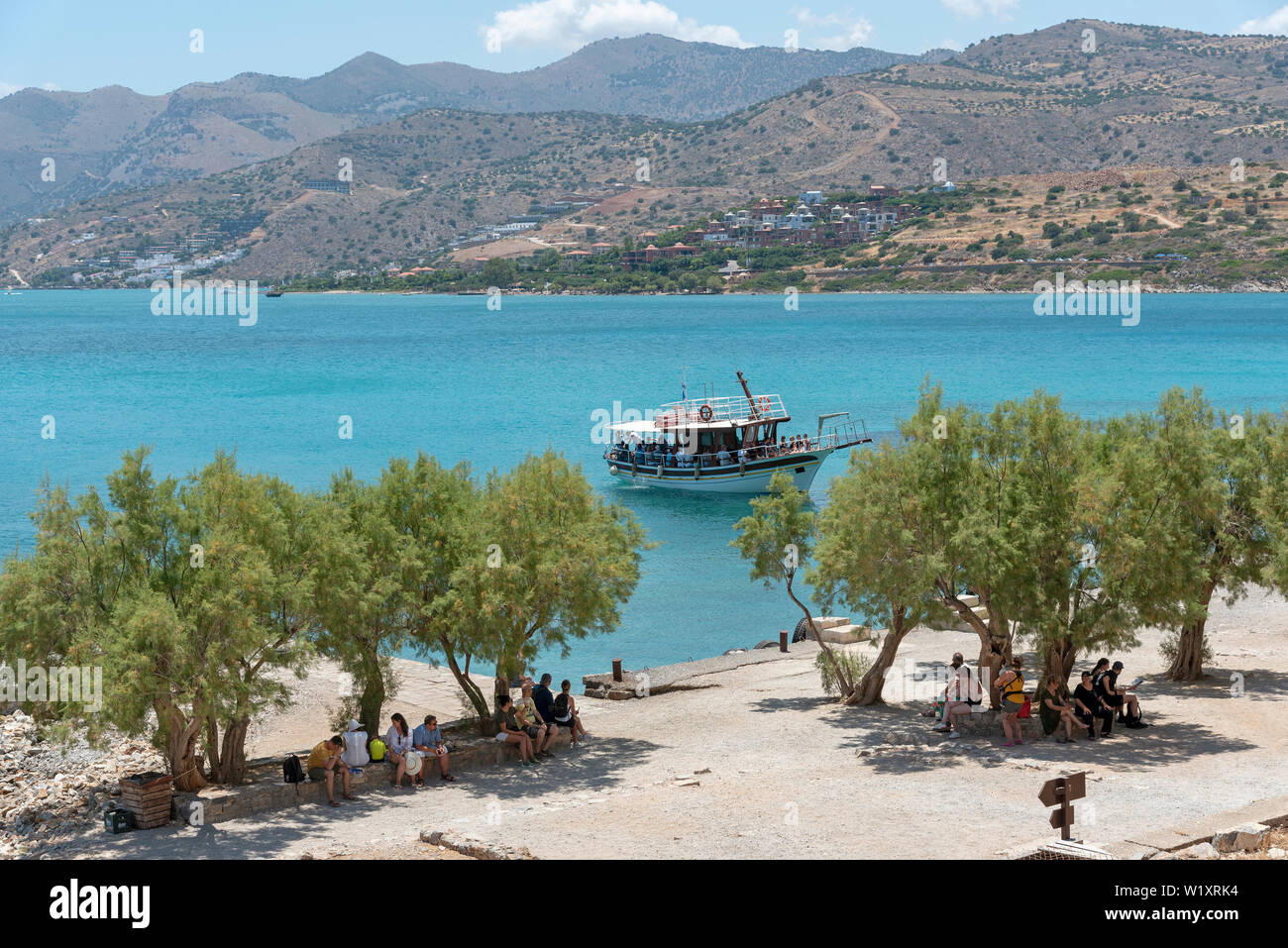 Spinalonga Island, Crete, Greece. June 2019.Small passenger ferry transporting tourists to Spinalonga a former Leper Colony. Background of mainland Cr - Stock Image