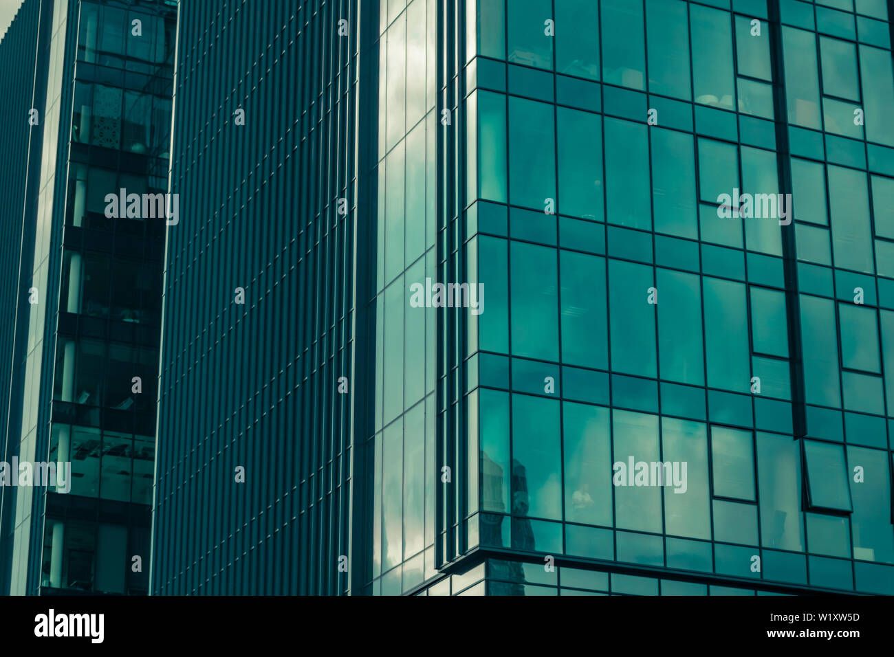 Sky with clouds reflected in windows of modern office building. Business background. Stock Photo