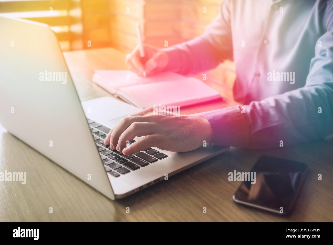 Businessman typing in information on a laptop or browsing the internet as he makes notes in a journal on the desk Stock Photo