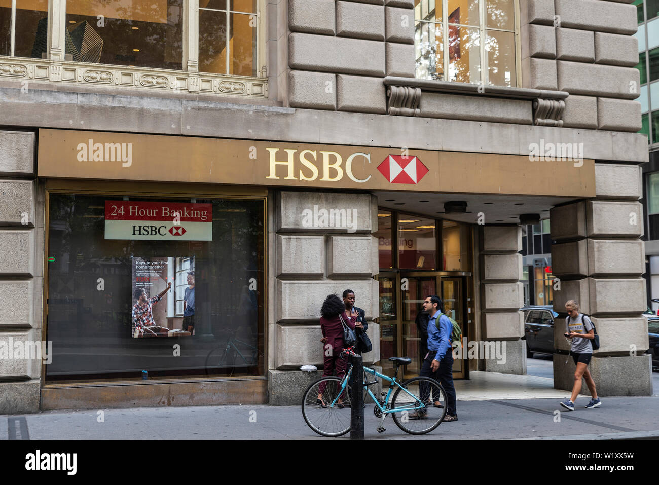 New York City, USA - August 1, 2018: Facade of a bank branch of HSBC with people around in Manhattan, New York City, USA - Stock Image