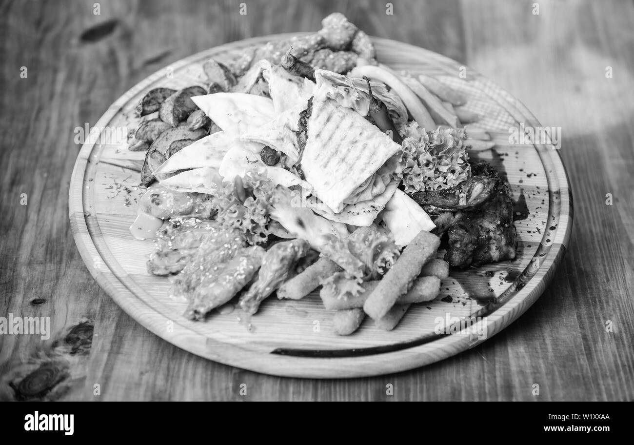 Pub menu snack. Tasty delicious snacks. Snack for beer. Restaurant food. Wooden board with lot french fries fish sticks burrito and meat steak served with salad. High calorie snack for group friends. - Stock Image