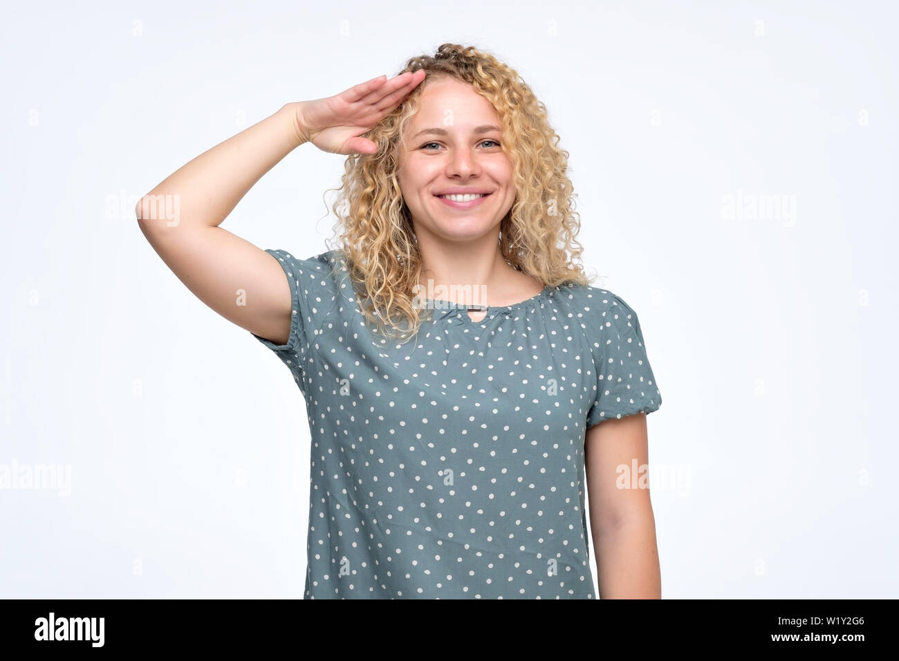 Woman with curly hairstyle looking at camera with salute and ready to do order - Stock Image