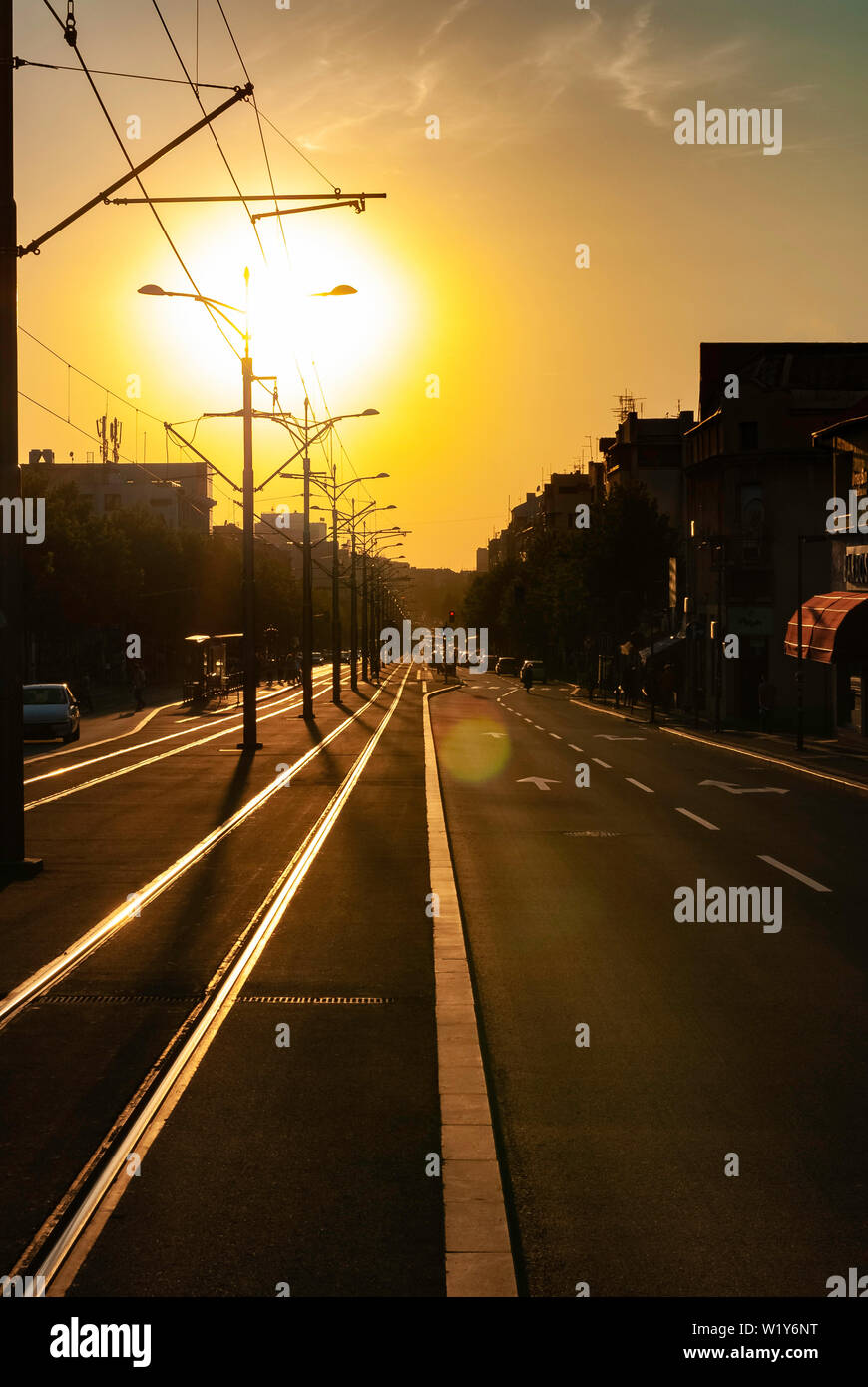 Urban city sunset vertical image of city street boulevard direct sunlight lens flare tram track tramway rails empty street trolleycar path Stock Photo