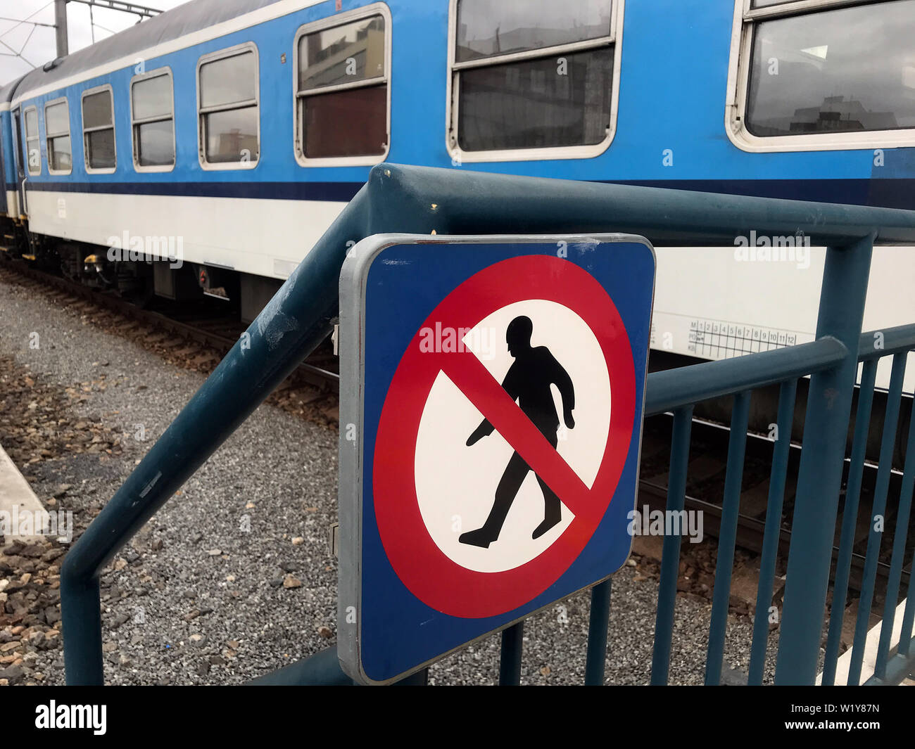 Signs for prohibition of walking on the track, the train is standing on the tracks in the background. - Stock Image