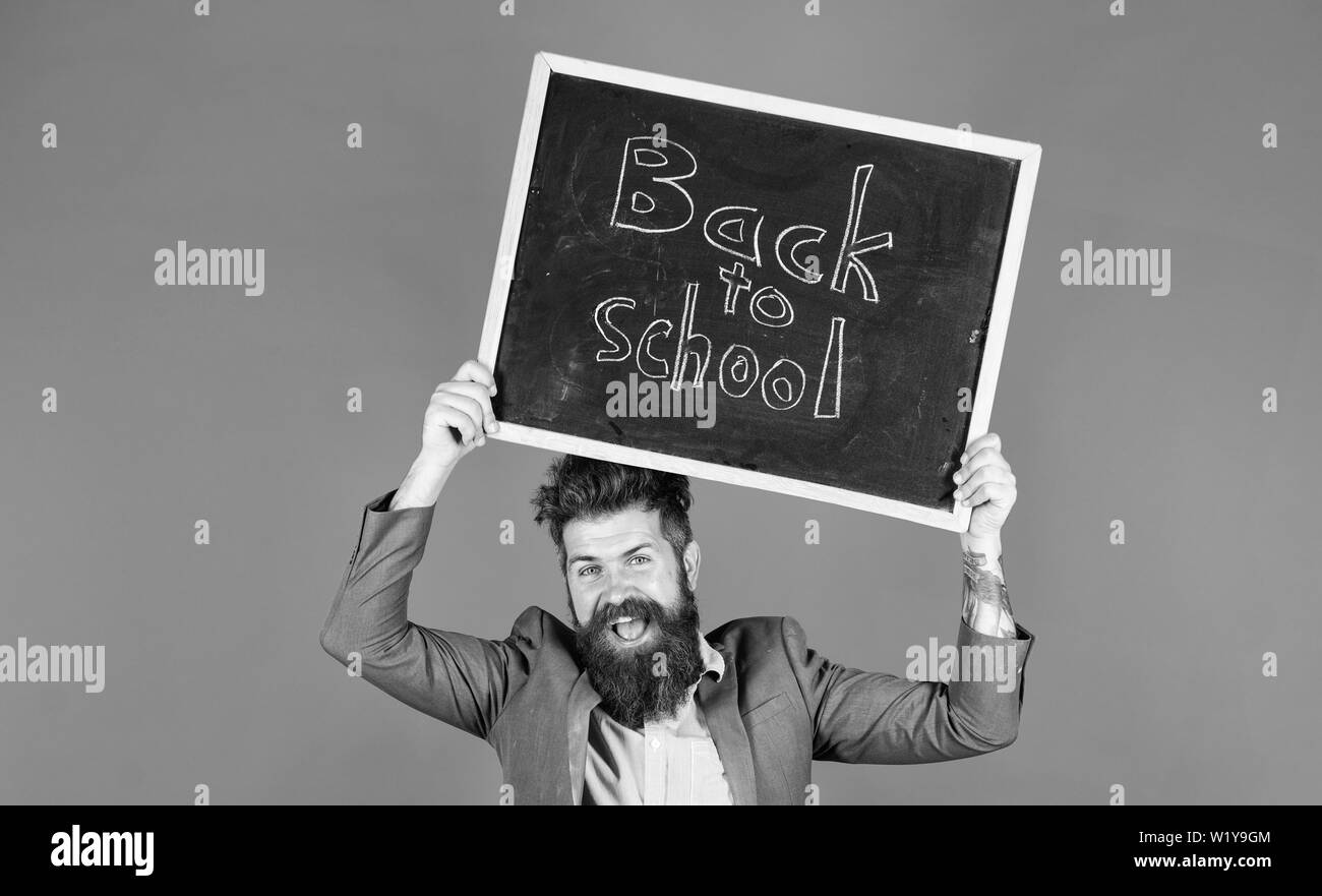 Stay positive. Keep working and be kind to people. Teacher bearded man holds blackboard with inscription back to school blue background. Teacher with tousled hair cheerful about school year beginning. - Stock Image
