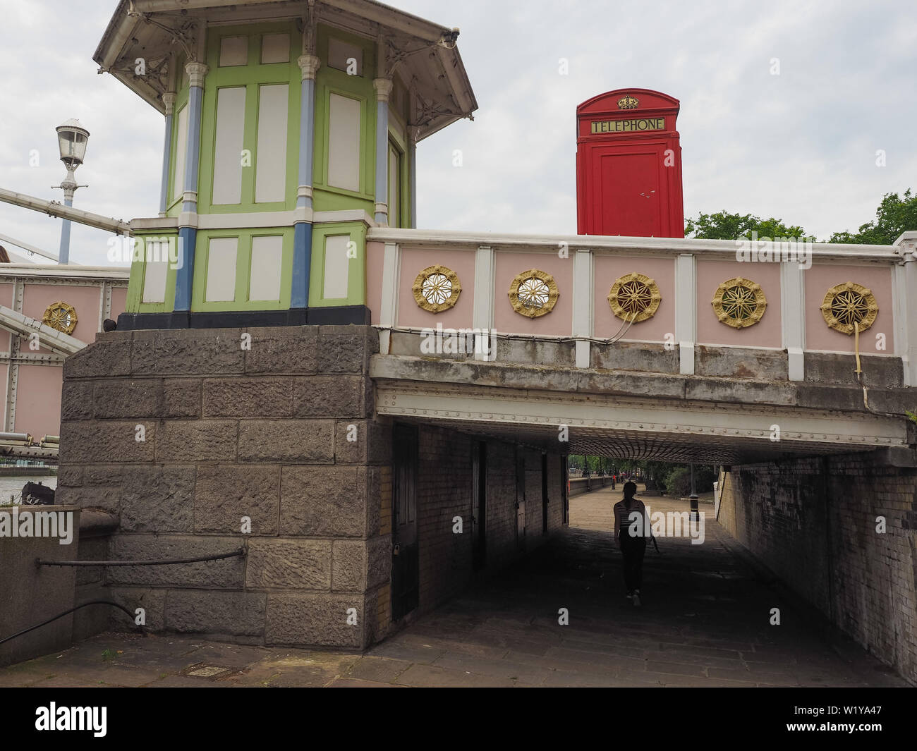 LONDON, UK - CIRCA JUNE 2019: Red telephone box on Albert Bridge crossing River Thames - Stock Image