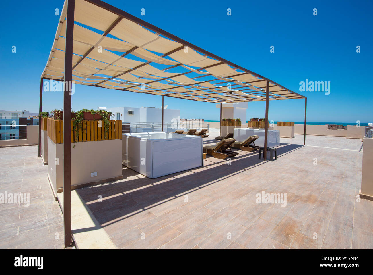Sunbeds And Hot Tubs On Roof Terrace Patio Sunbathing Area Of Luxury Hotel Apartment Building Stock Photo Alamy