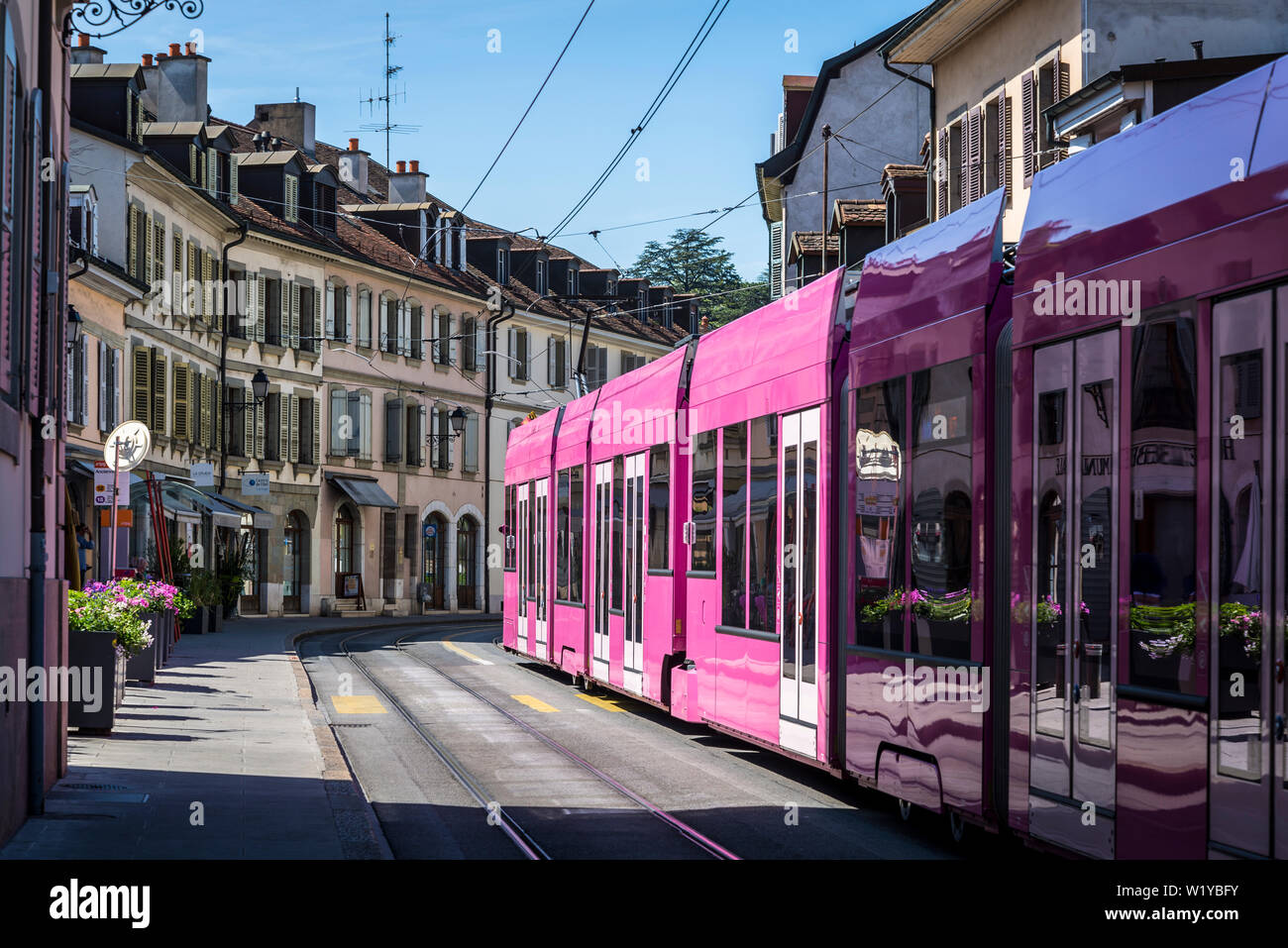 Tram passing through a typical street with  French-Italian architecture in the Carouge district, a Mediterranean style district modelled after Nice, G Stock Photo