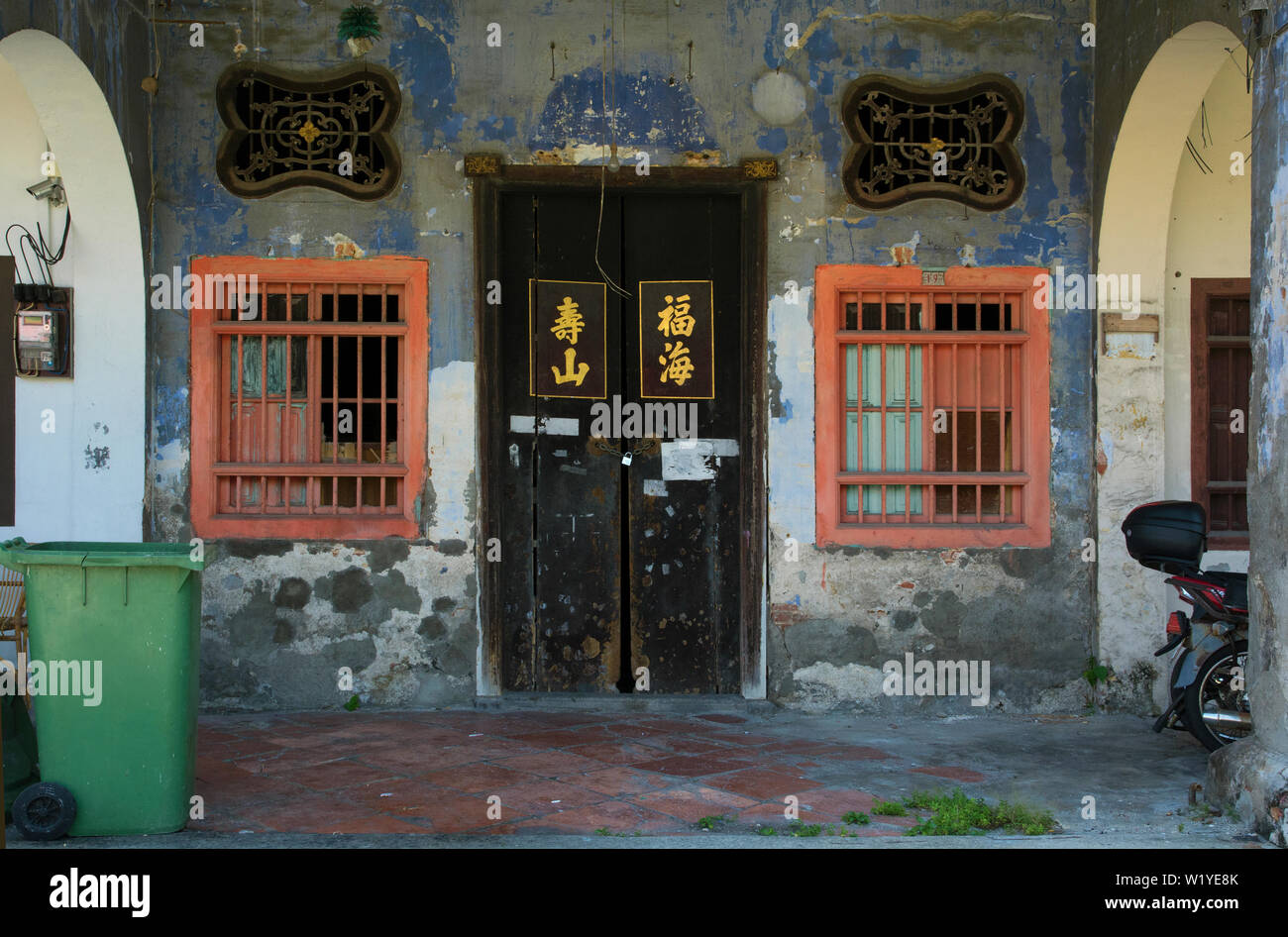 george town, penang/malaysia - february 24, 2017:  facade, wooden door and windows of a traditional chinese shophouse, five foot walk way - Stock Image