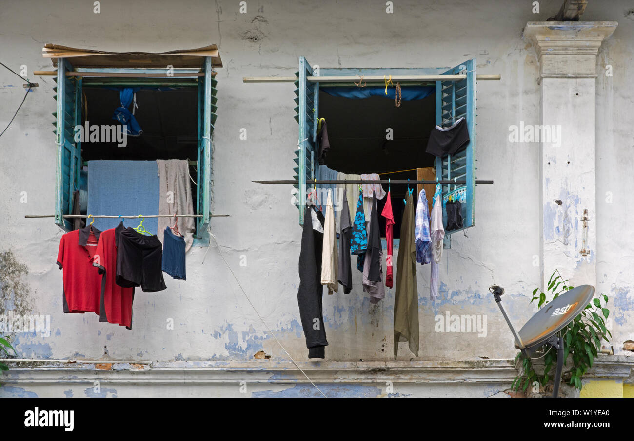 kuching, sarawak/malaysia - january 26, 2017: the facade and windows of an old chinese shophouse on jalan carpenter, laundry hanging at sticks for dry - Stock Image