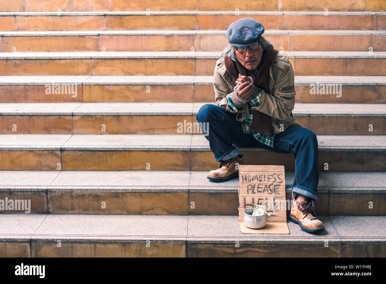 Dirty homeless person sitting on stairs with dollar cash in can, cold and lonely - Stock Image