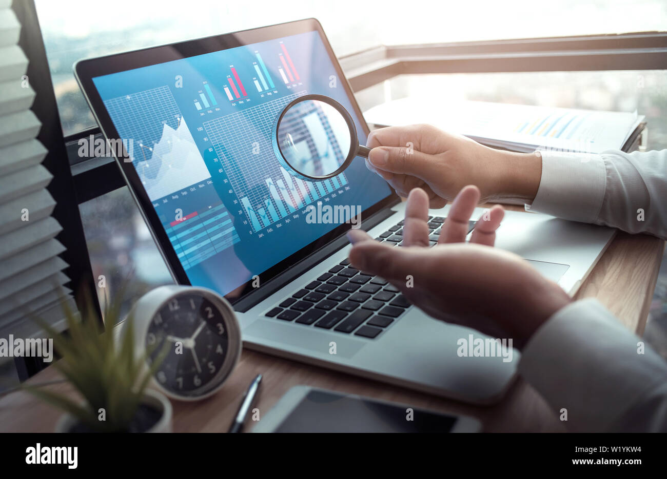 Business concepts with businessman holding magnifying glass with graph chart on computer laptop.For investment analysis,research market ideas Stock Photo