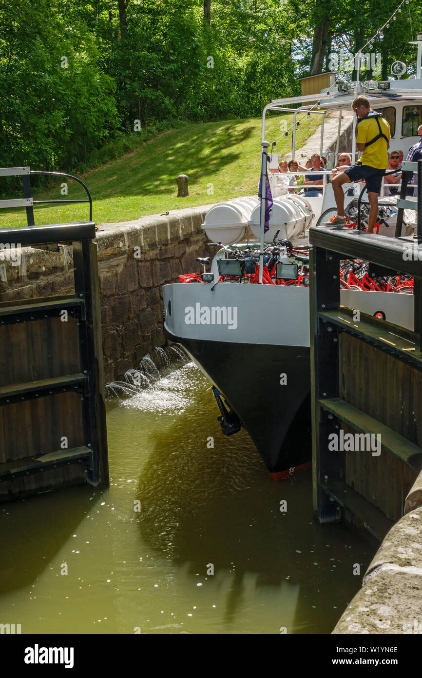 Lock gate that opens to a ship and a lock-keeper - Stock Image