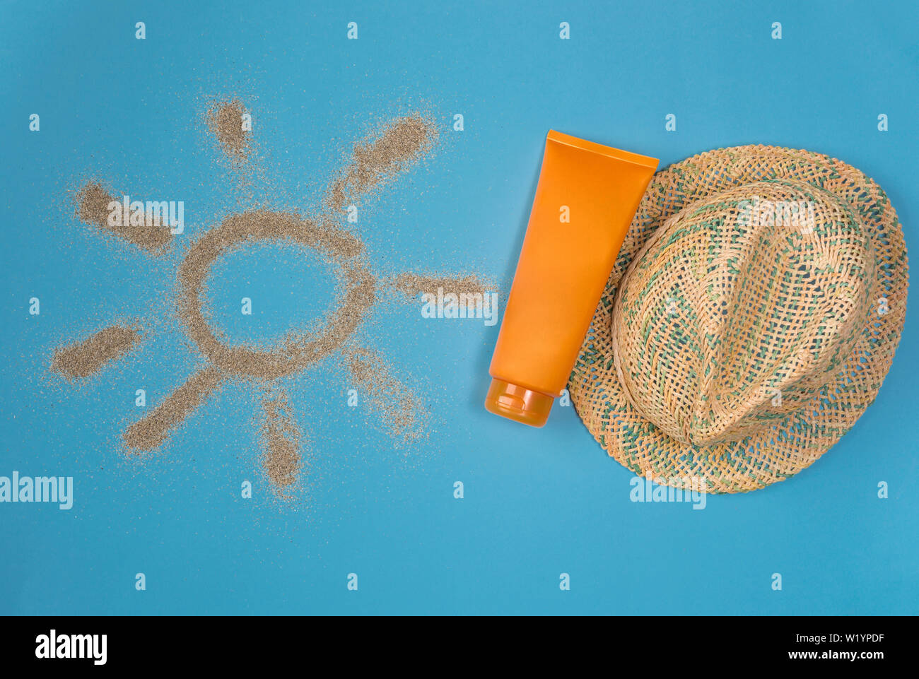 Sunscreens isolated on blue background. Sun drawn by the sand on blue background. Top view. Stock Photo