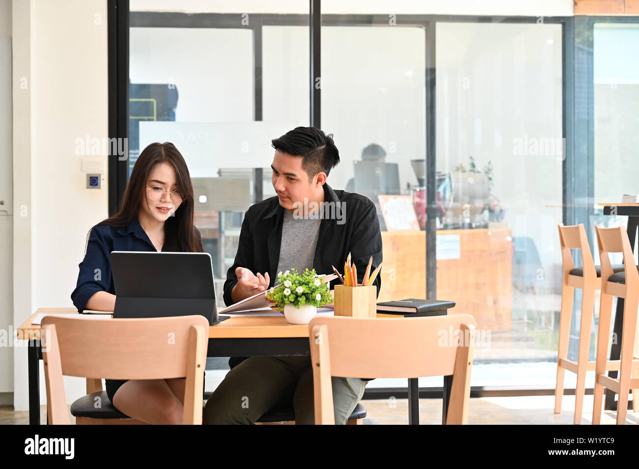 Two asian people working on co working cafe with talking startup business. - Stock Image