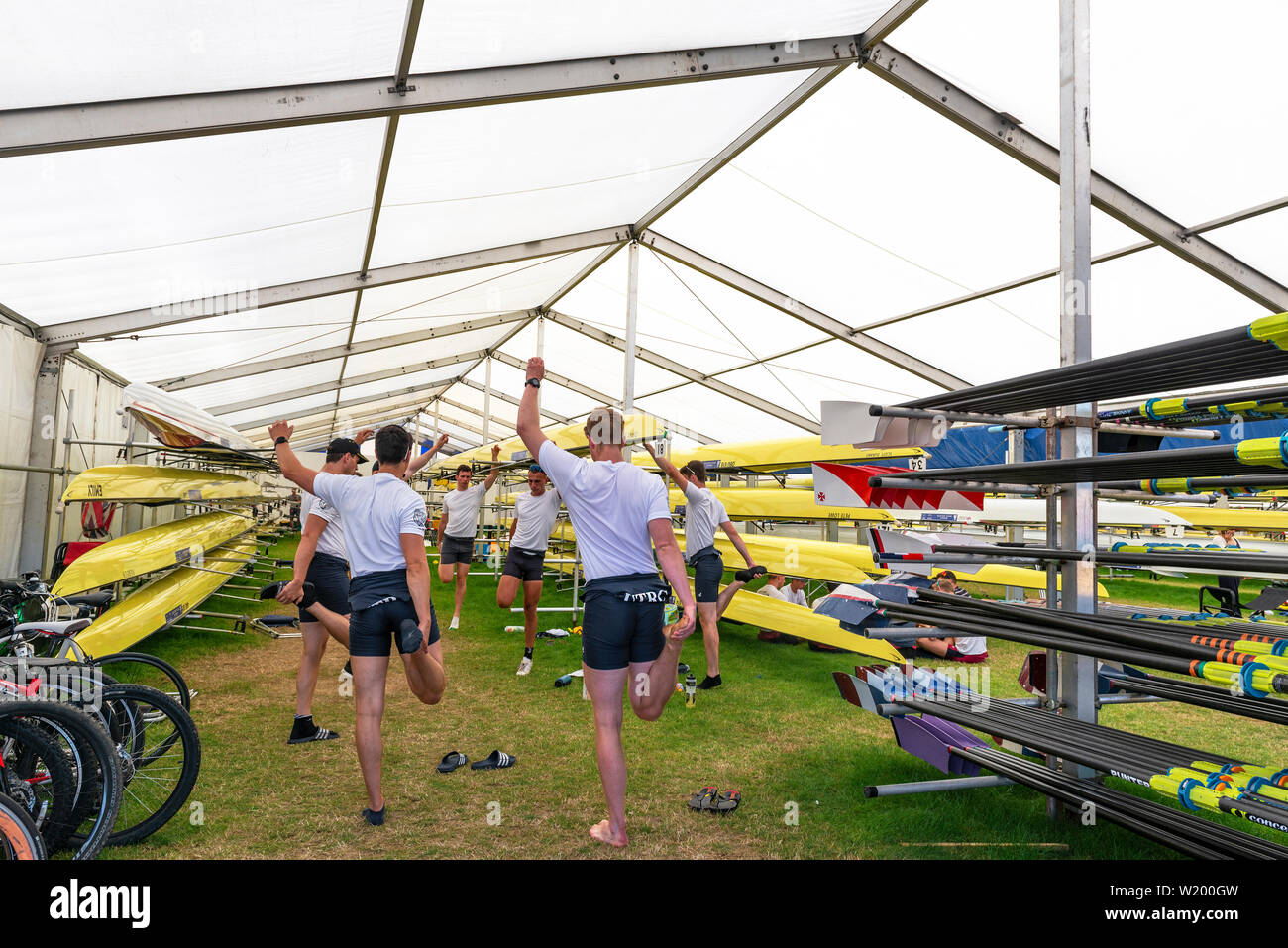 Henley on Thames, Berkshire, UK. 4th July, 2019. Henley Royal Regatta. Upper Thames  Rowing Club team limbering up with stretches in the boat tent before their race in the Thames Challenge Cup. Credit Gary Blake/Alamy Live - Stock Image