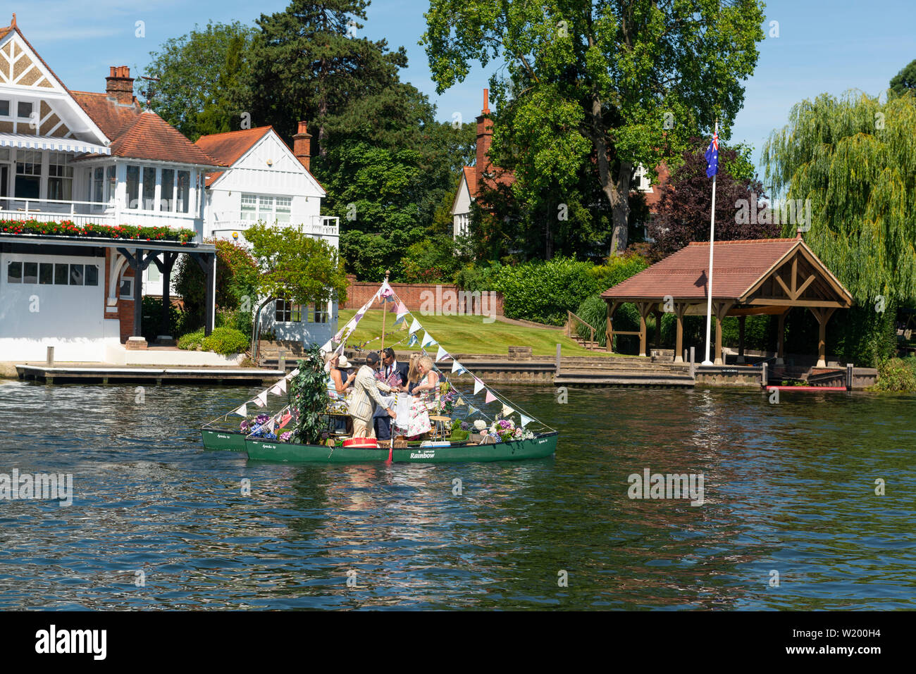 Henley on Thames, Berkshire, UK. 4th July, 2019. Henley Royal Regatta.Regatta spectators paddling a 'catamaran canoe' to moor up along  side  the wooden  boom separating the river traffic from the race on the River Thames  to view the afternoons  racing in style .Credit Gary Blake/Alamy Live - Stock Image